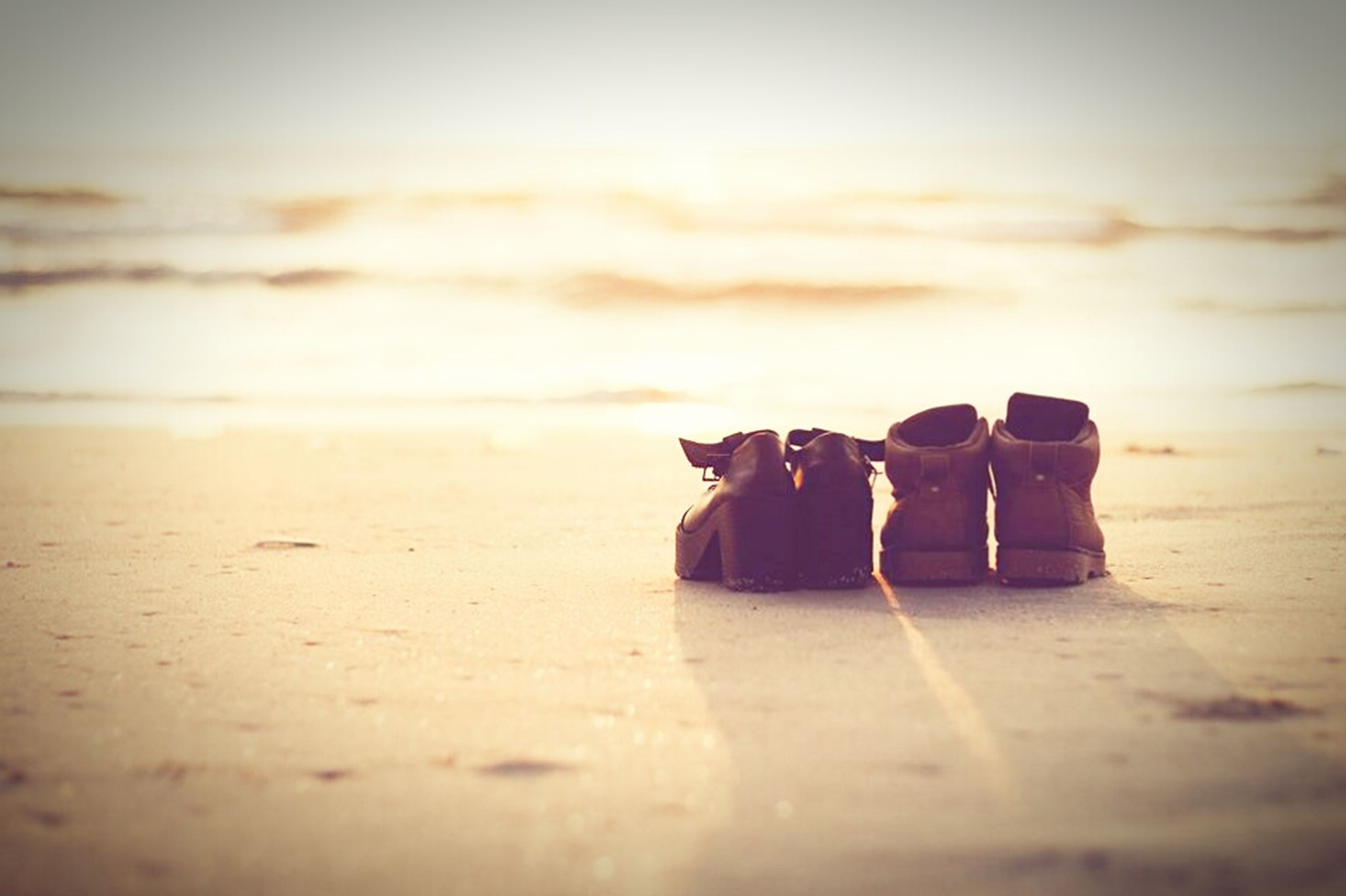 beach, sand, selective focus, in a row, sea, focus on foreground, still life, shore, surface level, tranquility, stack, absence, sky, close-up, side by side, table, no people, day, large group of objects, nature