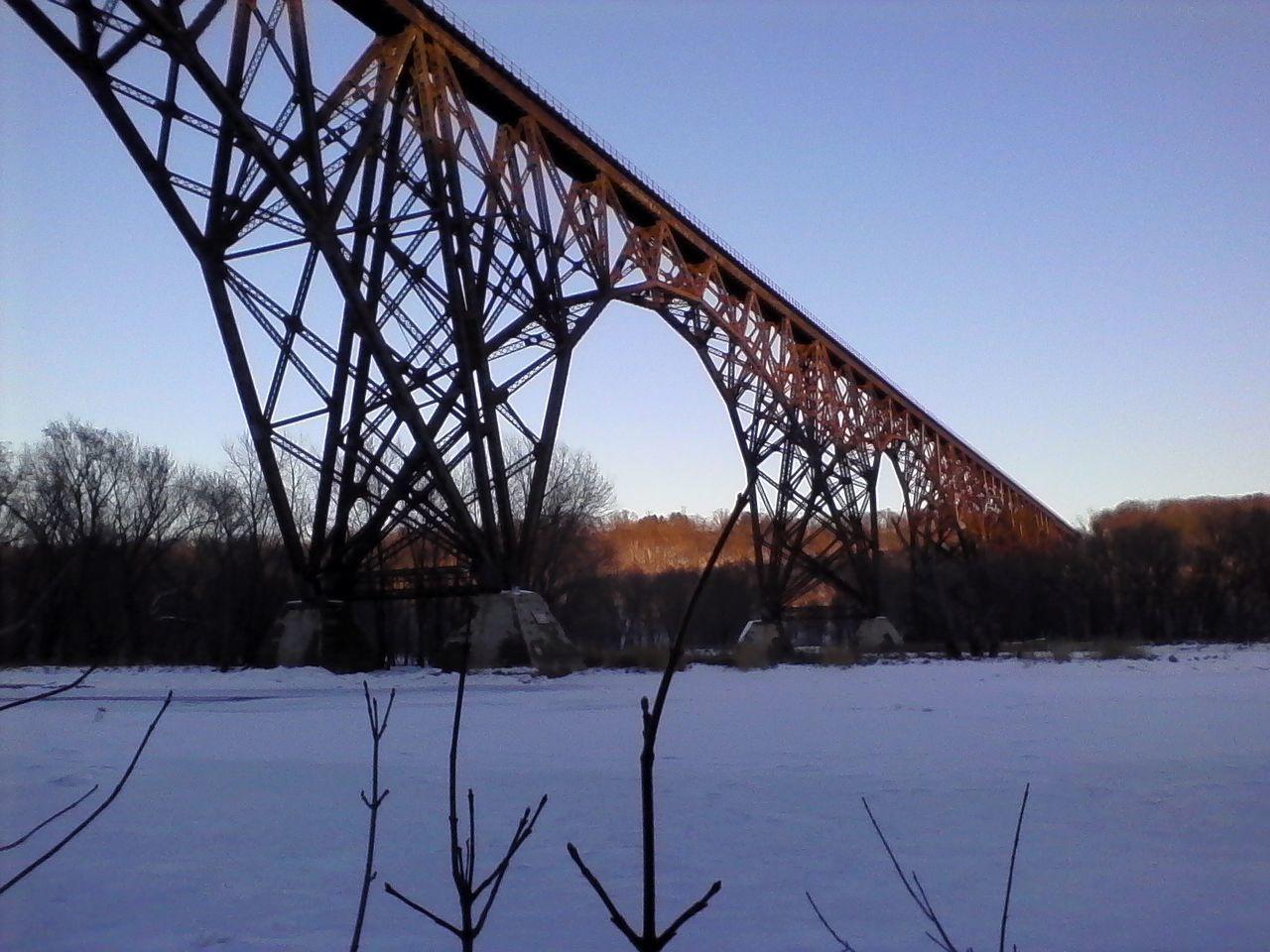 Low angle view of metallic bridge over frozen river