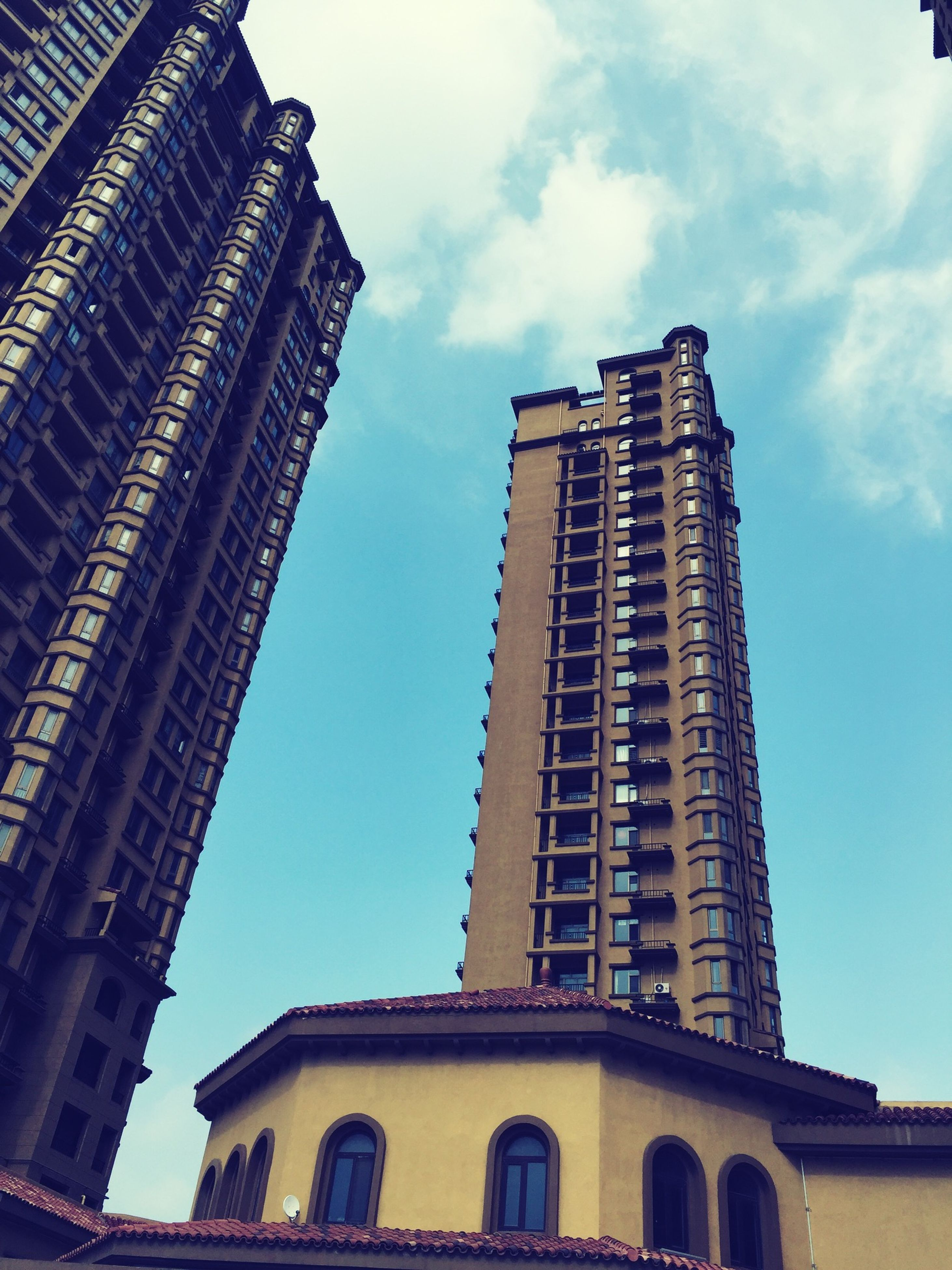 architecture, building exterior, built structure, low angle view, sky, city, building, window, tower, outdoors, cloud - sky, tall - high, day, cloud, no people, arch, travel destinations, history, city life, residential building