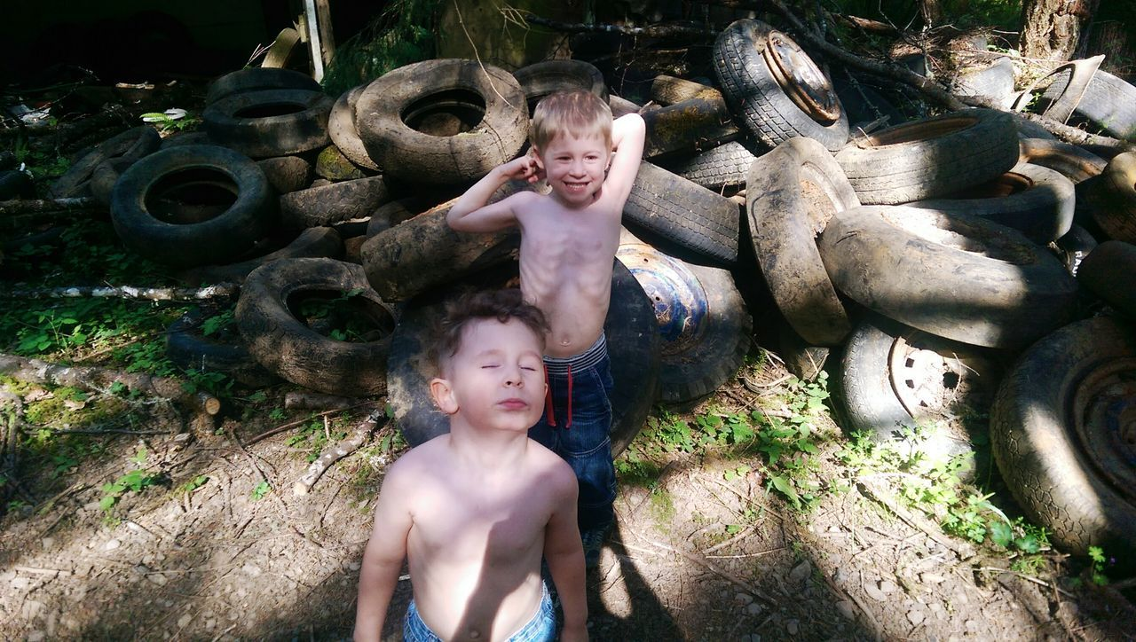 real people, childhood, boys, shirtless, front view, leisure activity, happiness, lifestyles, fun, elementary age, mouth open, outdoors, looking at camera, field, portrait, two people, casual clothing, smiling, day, standing, togetherness, young adult