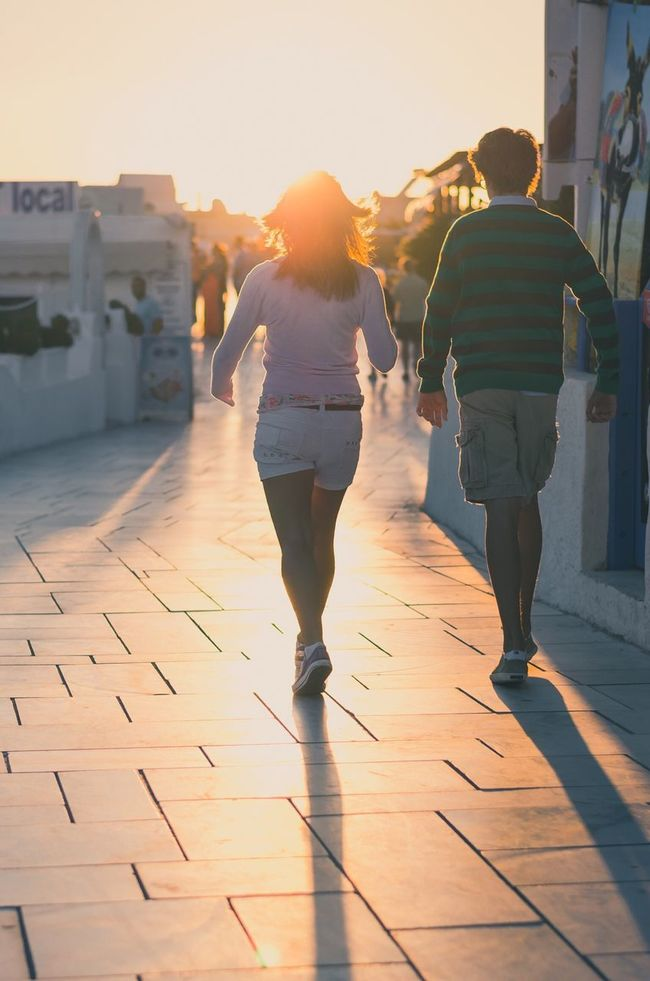 Hiking the iconic paths of Oia Santorini | Alternative Fitness Couple Travel Street Photography People Sunset Halo Effect Backlight Backlit Sunset Woman And Man Light And Shadow