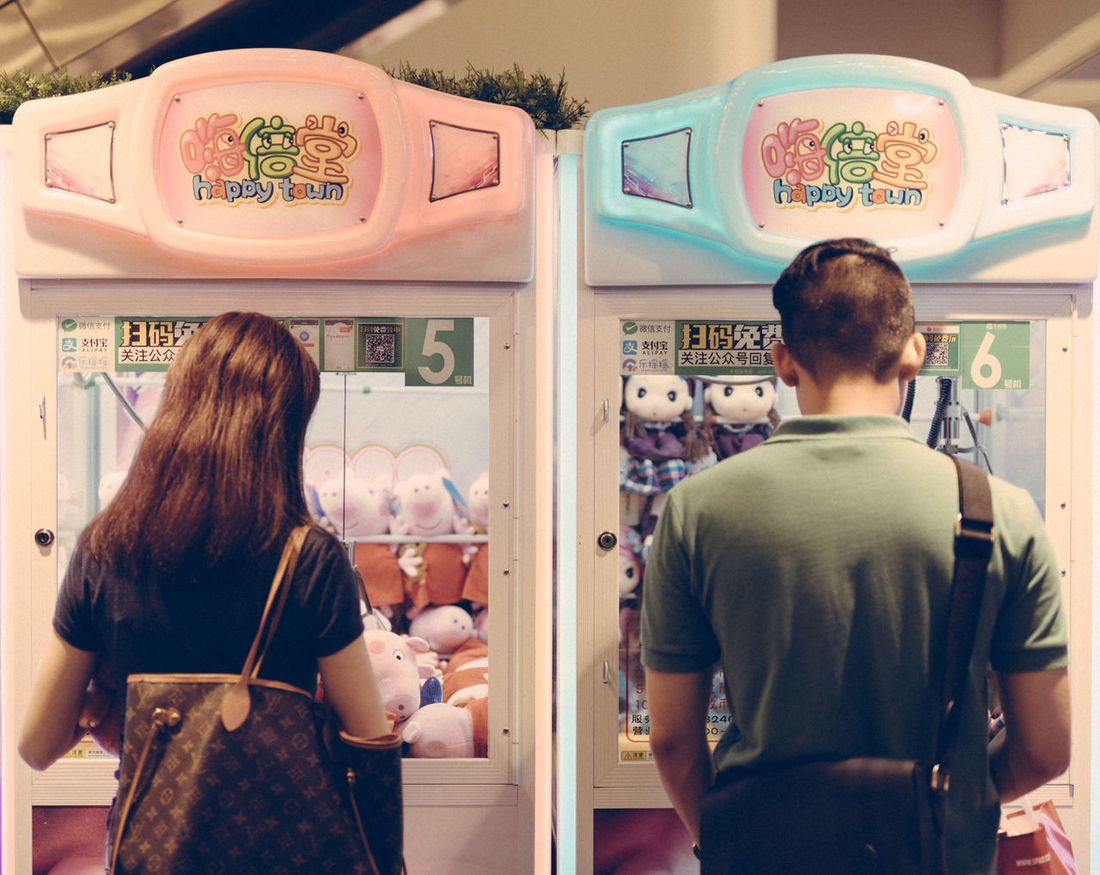 Playing claw crane game The Week On EyeEm Choice Claw Crane Claw Machine Customer  Day Game Indoors  Leisure Activity Men Mirror One Person People Price Tag Real People Rear View Reflection Retail  Standing Store Text Variation Vending Machine