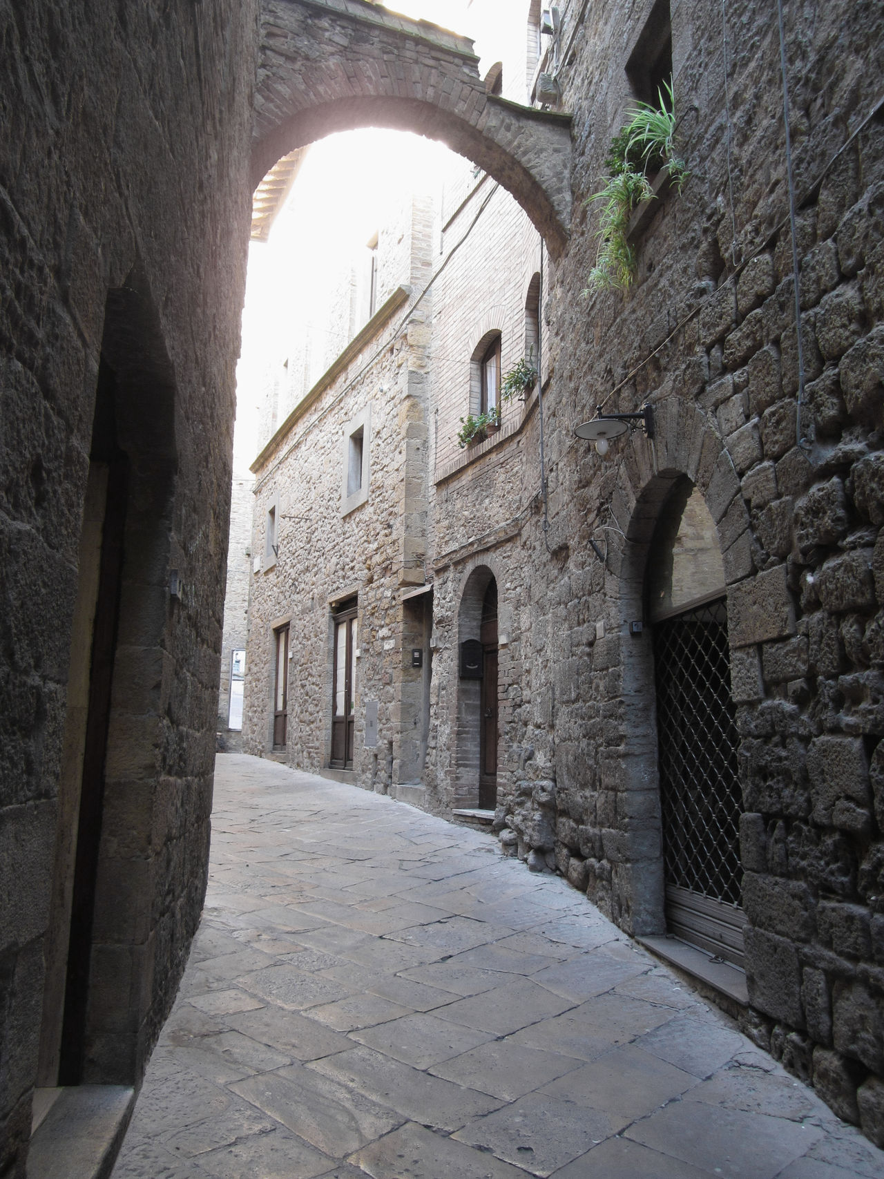 Hidden alley in Volterra village, province of Pisa . Tuscany, Italy Alabaster Alley Ancient Antique Arch Architecture Civilization Etruscan Hamlet High Hill Historic Italy Medieval Pisa Stony Street Tourism Town Travel Tuscany View Village Volterra Wall