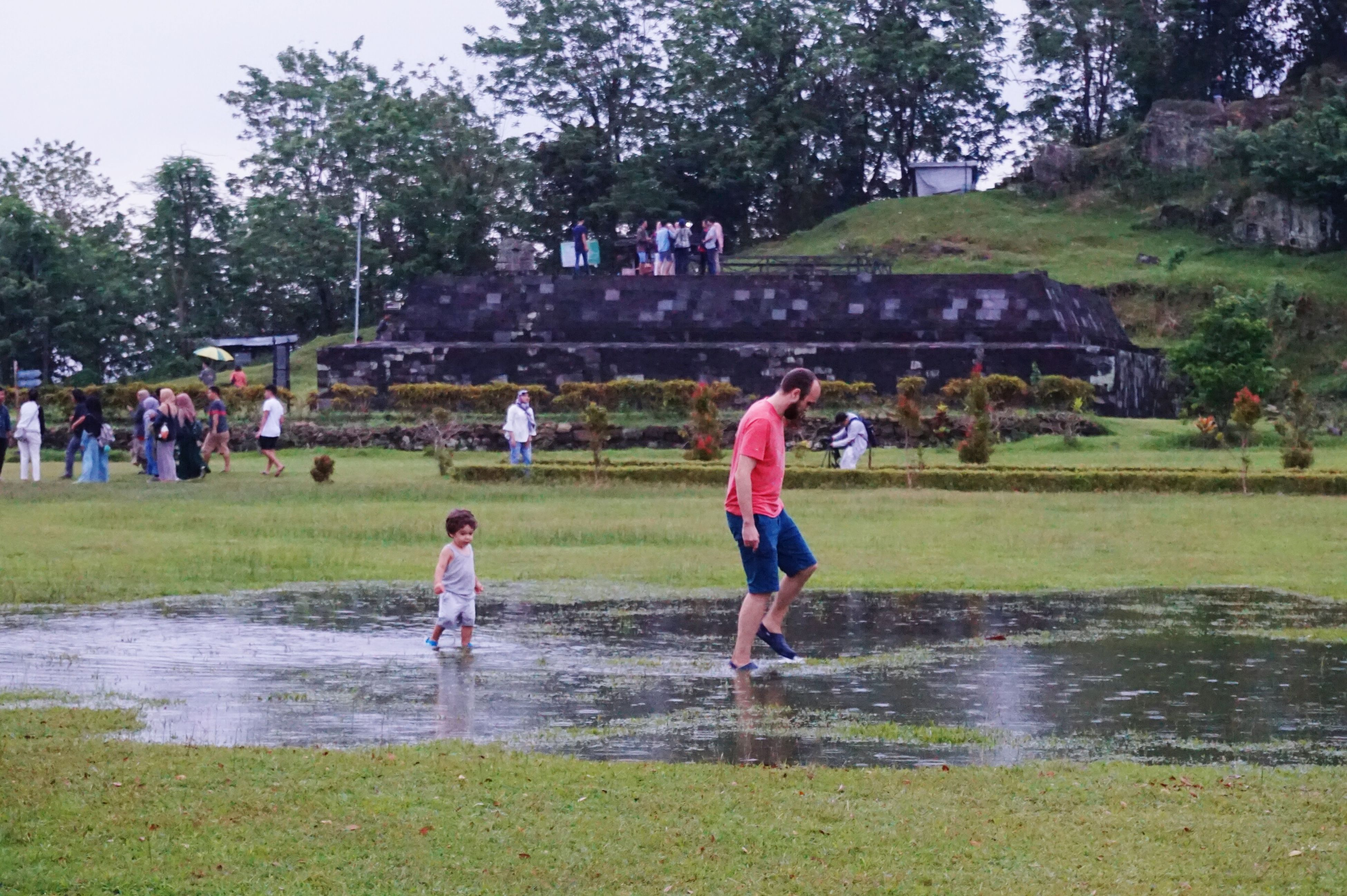 water, playing, grass, fun, leisure activity, boys, childhood, spraying, tree, enjoyment, full length, outdoors, real people, day, lifestyles, wet, park - man made space, girls, nature, motion, togetherness, large group of people, men, child, sky, people, adult