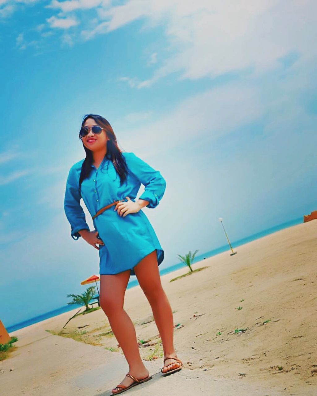 sunglasses, beach, young adult, real people, full length, young women, one person, sea, sand, leisure activity, standing, outdoors, beautiful woman, nature, lifestyles, front view, sky, beauty in nature, day, casual clothing, vacations, water, blue, scenics, horizon over water, posing, portrait