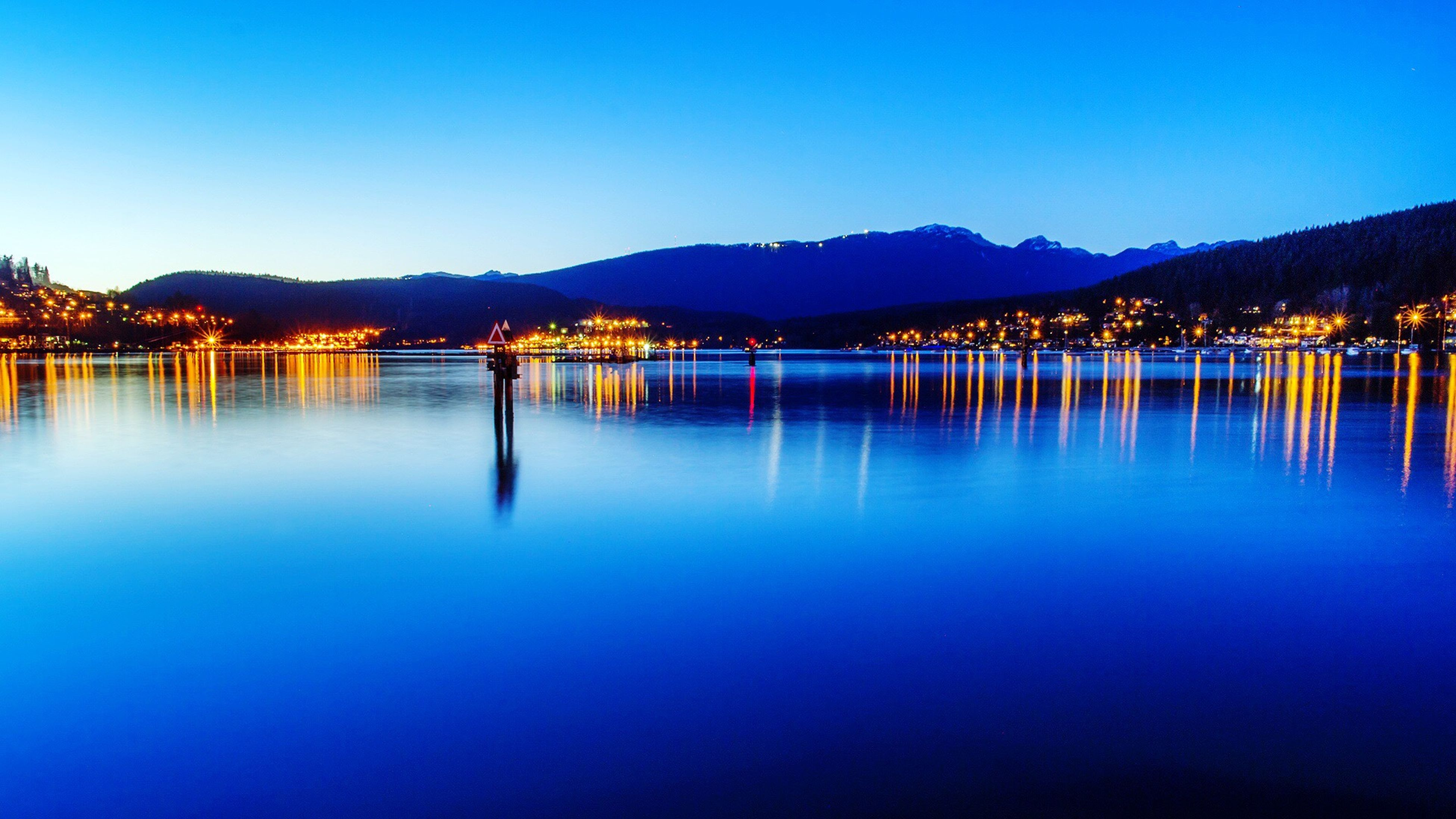 Scenic View Of Lake By Illuminated City And Mountains