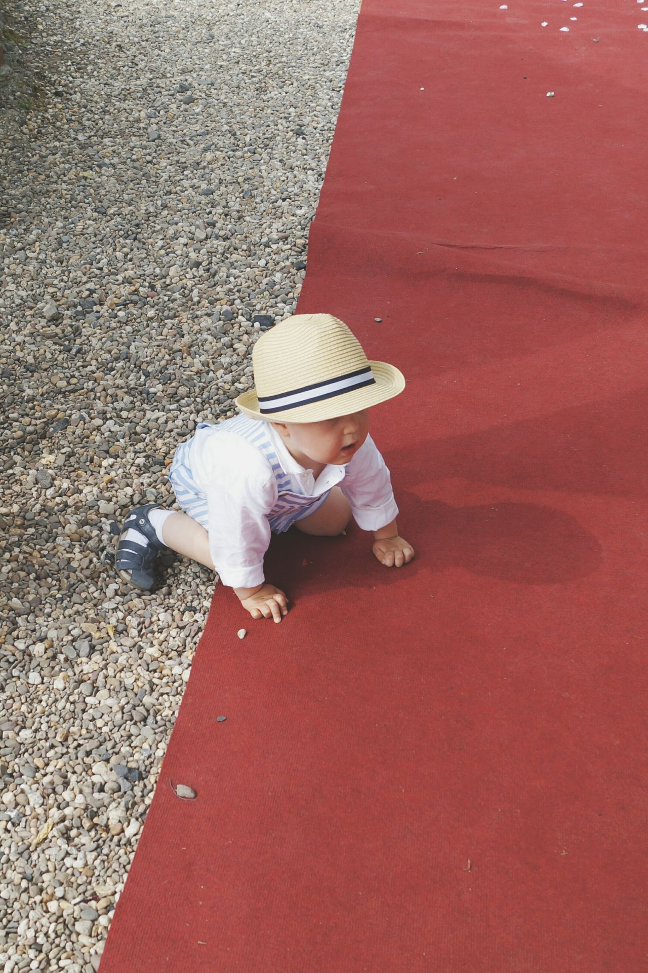 Exploring Toddler  Babyboy Sitting Crawling On The Floor Red Carpet Gravel Path Pebbles Childrens Clothing Hat Exploring Curiosity Child Wedding Dressed Up Looking Down EyeEm Best Shots From My Point Of View Happy Day Outdoors The Street Photographer - 2016 EyeEm Awards Playing EyeEm Best Edits Boy The Photojournalist - 2016 EyeEm Awards