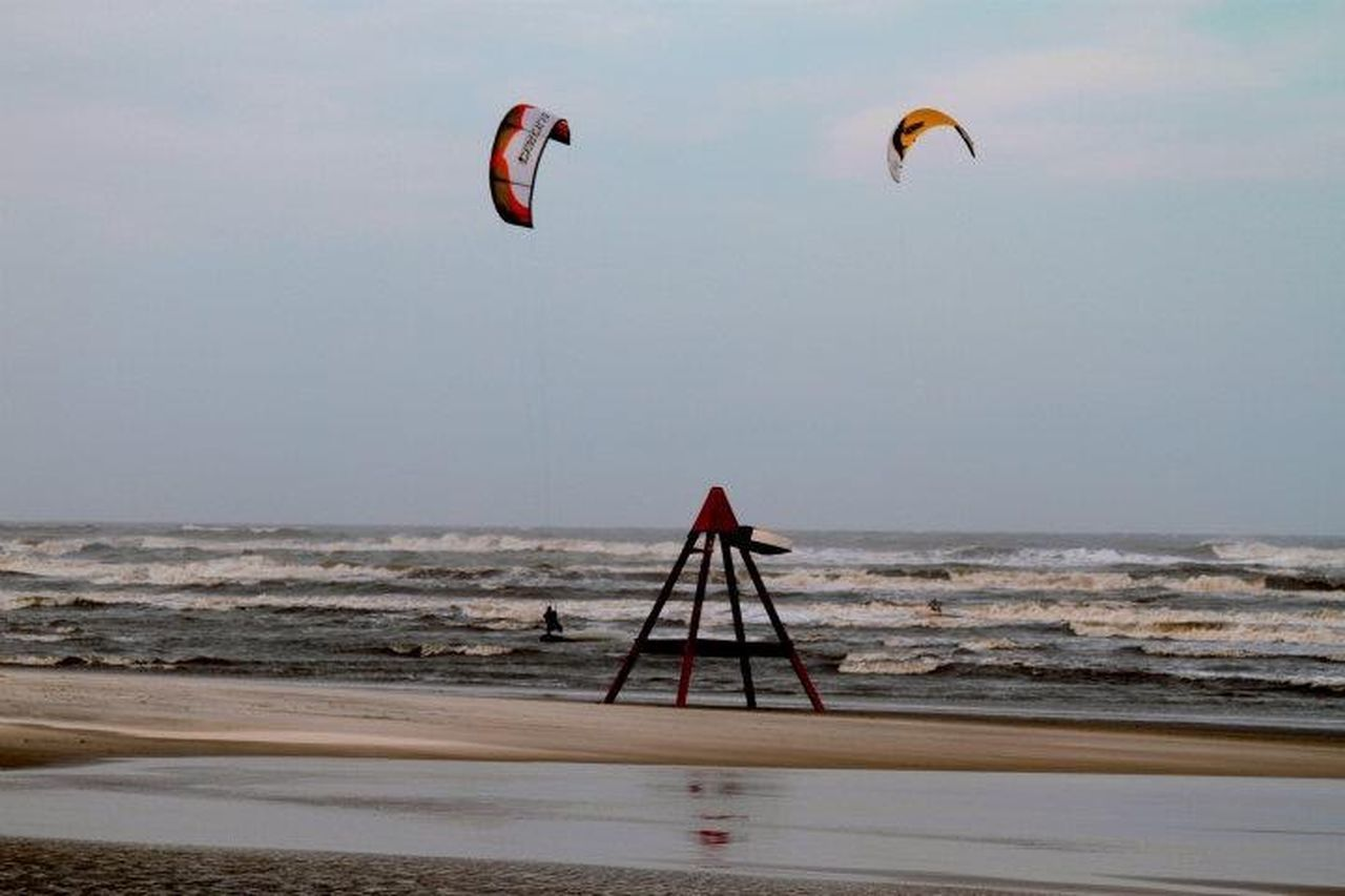 sea, beach, horizon over water, parachute, adventure, leisure activity, sky, nature, extreme sports, water, day, sand, sport, outdoors, scenics, beauty in nature, paragliding, wave, clear sky, flying, no people