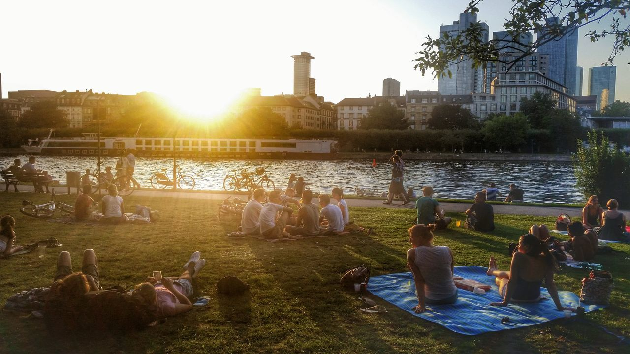 People Relaxing On Riverbank At Sunset