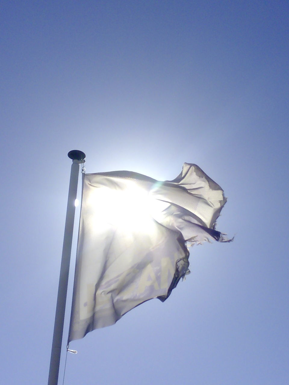 low angle view, flag, copy space, clear sky, no people, outdoors, day, blue, sunlight, patriotism, statue, sky, close-up