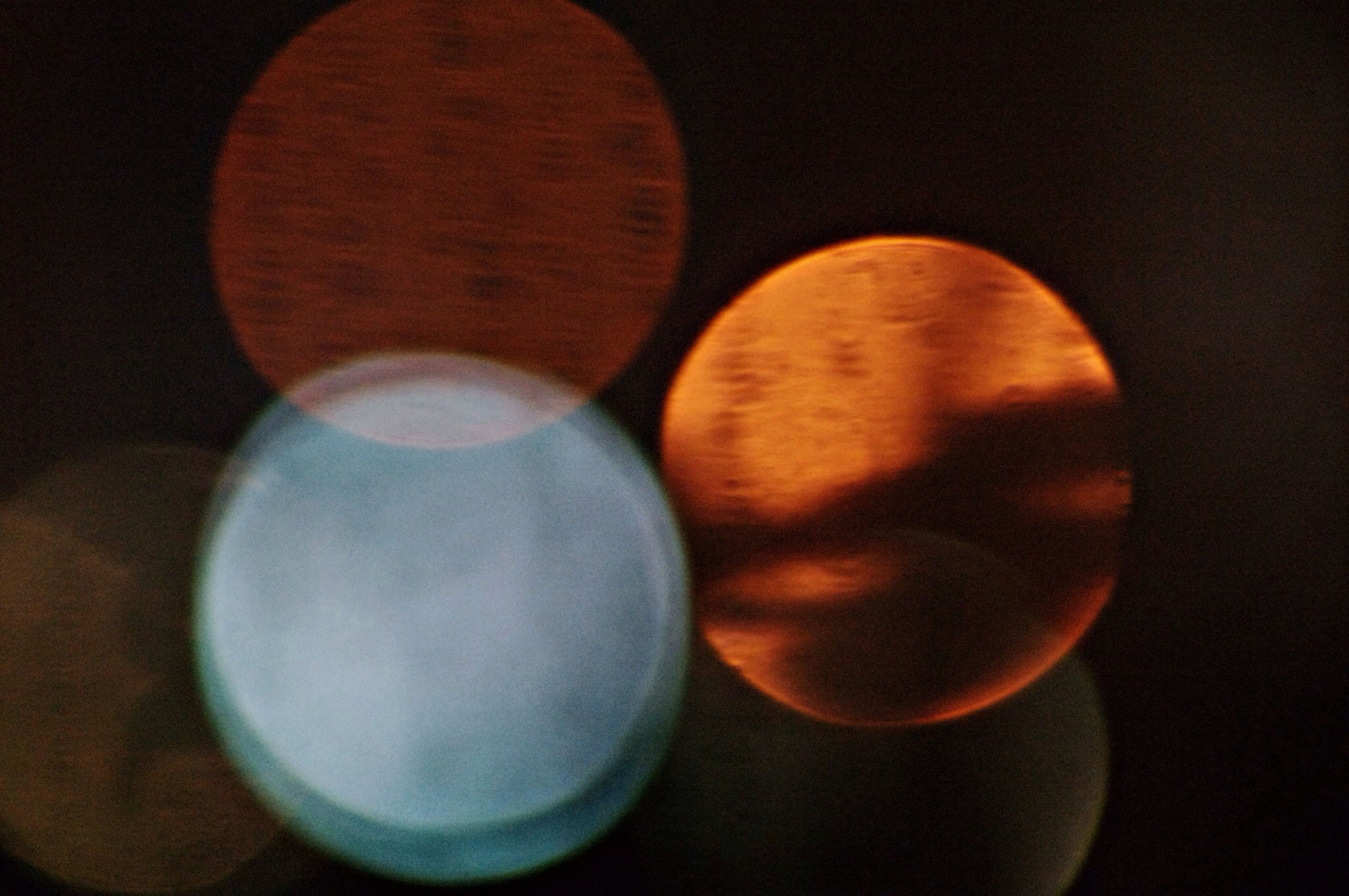 circle, indoors, close-up, still life, illuminated, night, geometric shape, sphere, no people, orange color, shape, dark, table, round, lighting equipment, high angle view, pattern, light - natural phenomenon, glowing, studio shot