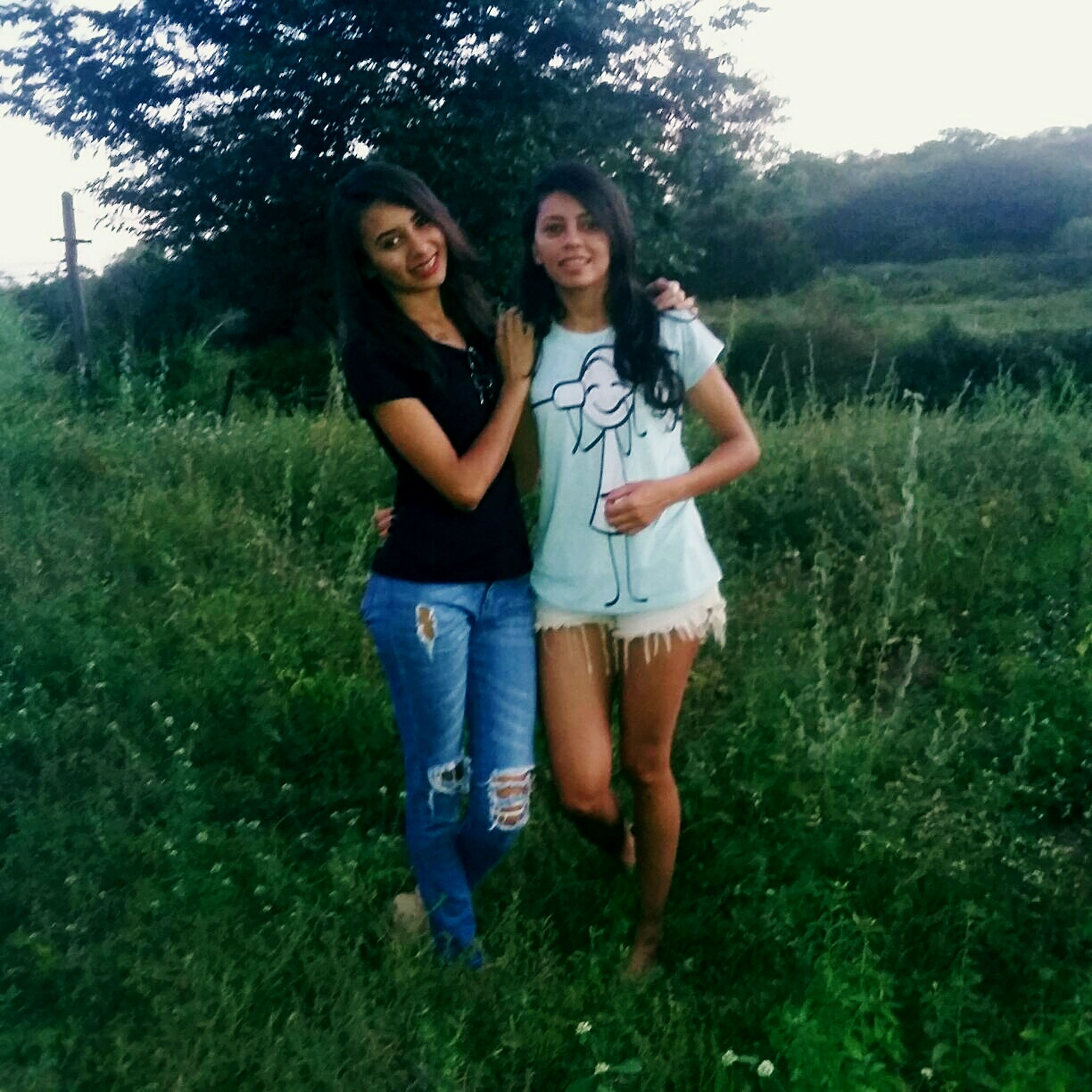 grass, casual clothing, real people, full length, front view, standing, togetherness, smiling, happiness, leisure activity, two people, young women, young adult, outdoors, day, bonding, tree, lifestyles, growth, friendship, looking at camera, nature, portrait