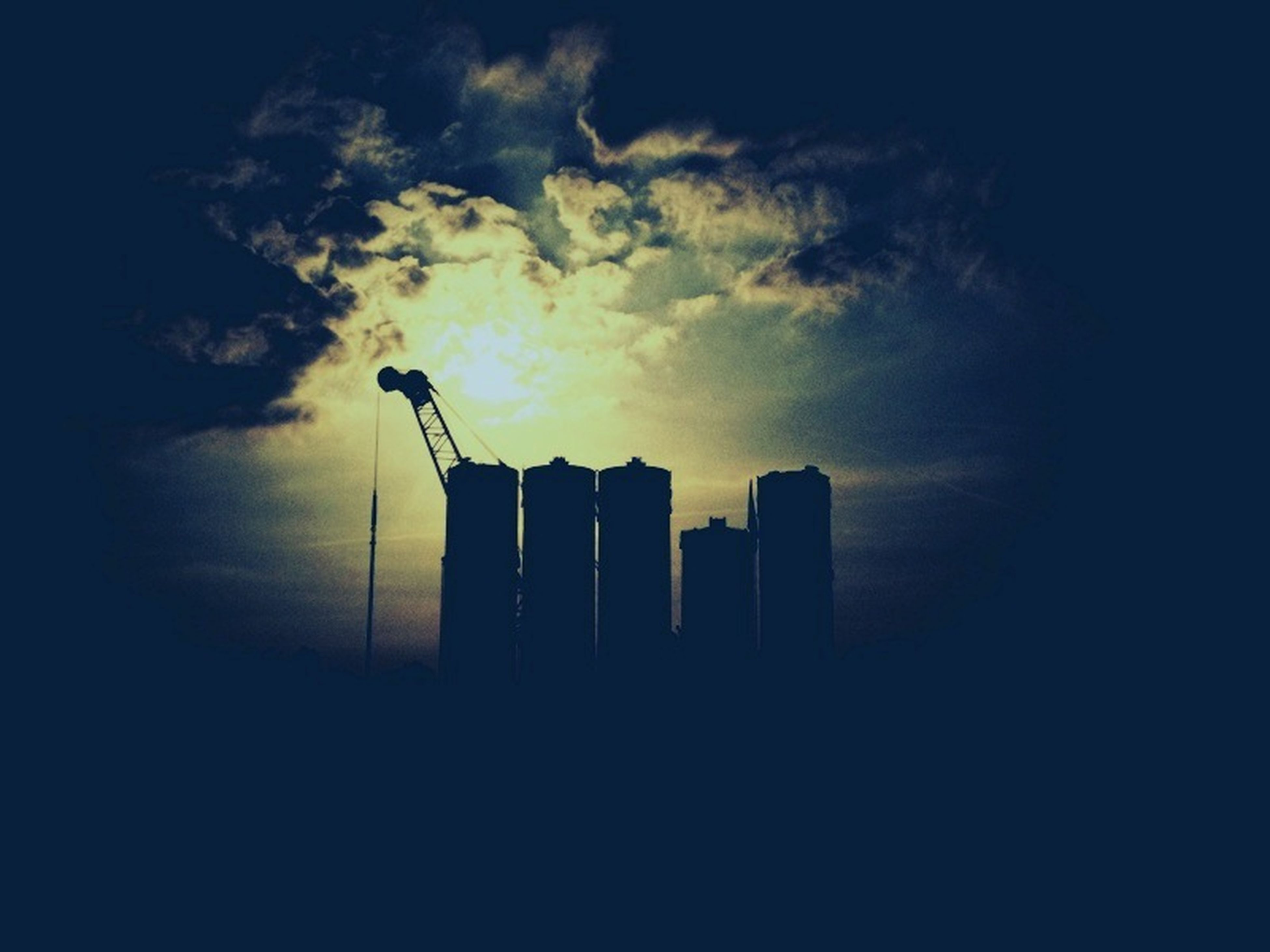 sky, building exterior, architecture, built structure, silhouette, low angle view, cloud - sky, sunset, cloudy, tower, tall - high, city, dusk, skyscraper, building, cloud, outdoors, dark, no people, weather