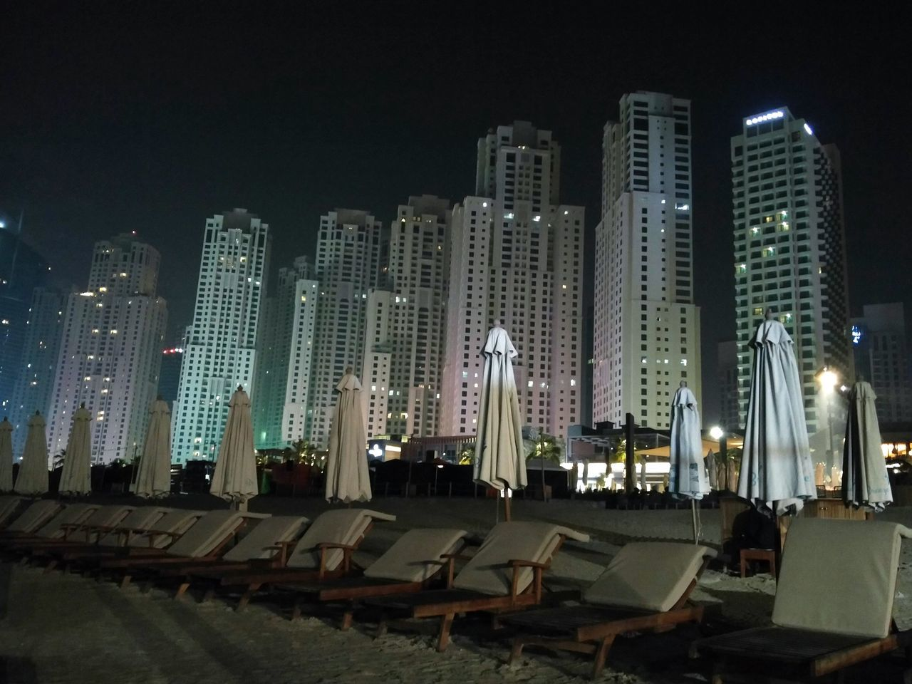 Night Urban Skyline Skyscraper City Building Exterior Architecture Illuminated Business Finance And Industry Outdoors Sky Cityscape Transportation No People Futuristic City Life Built Structure Downtown District Modern Office Building Exterior Dubai Dubaimarinawalk Beachatnight Parasols