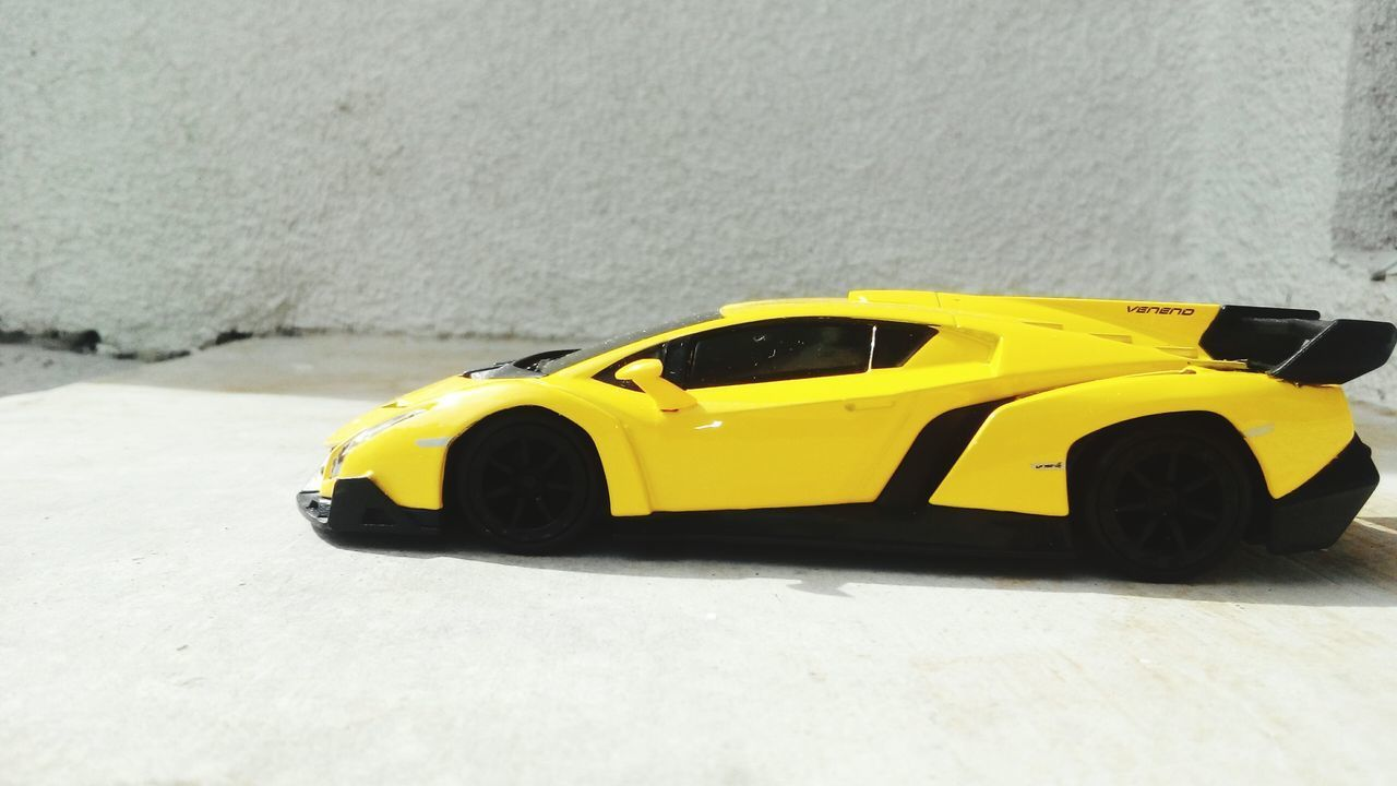 yellow, car, transportation, toy, taxi, surface level, toy car, land vehicle, street, yellow taxi, childhood, day, no people, close-up, outdoors, racecar