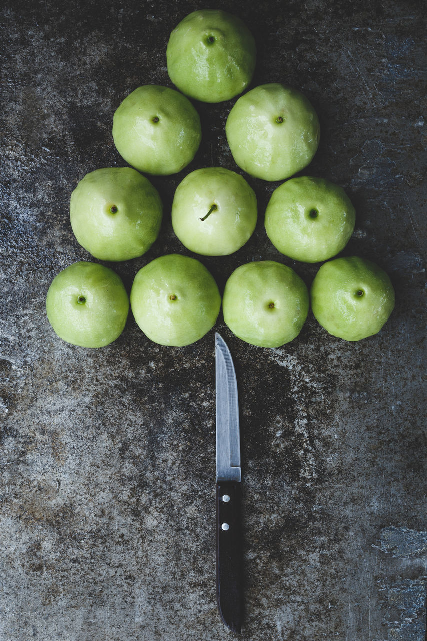 High Angle View Of Green Plums With Knife Arranged On Slate