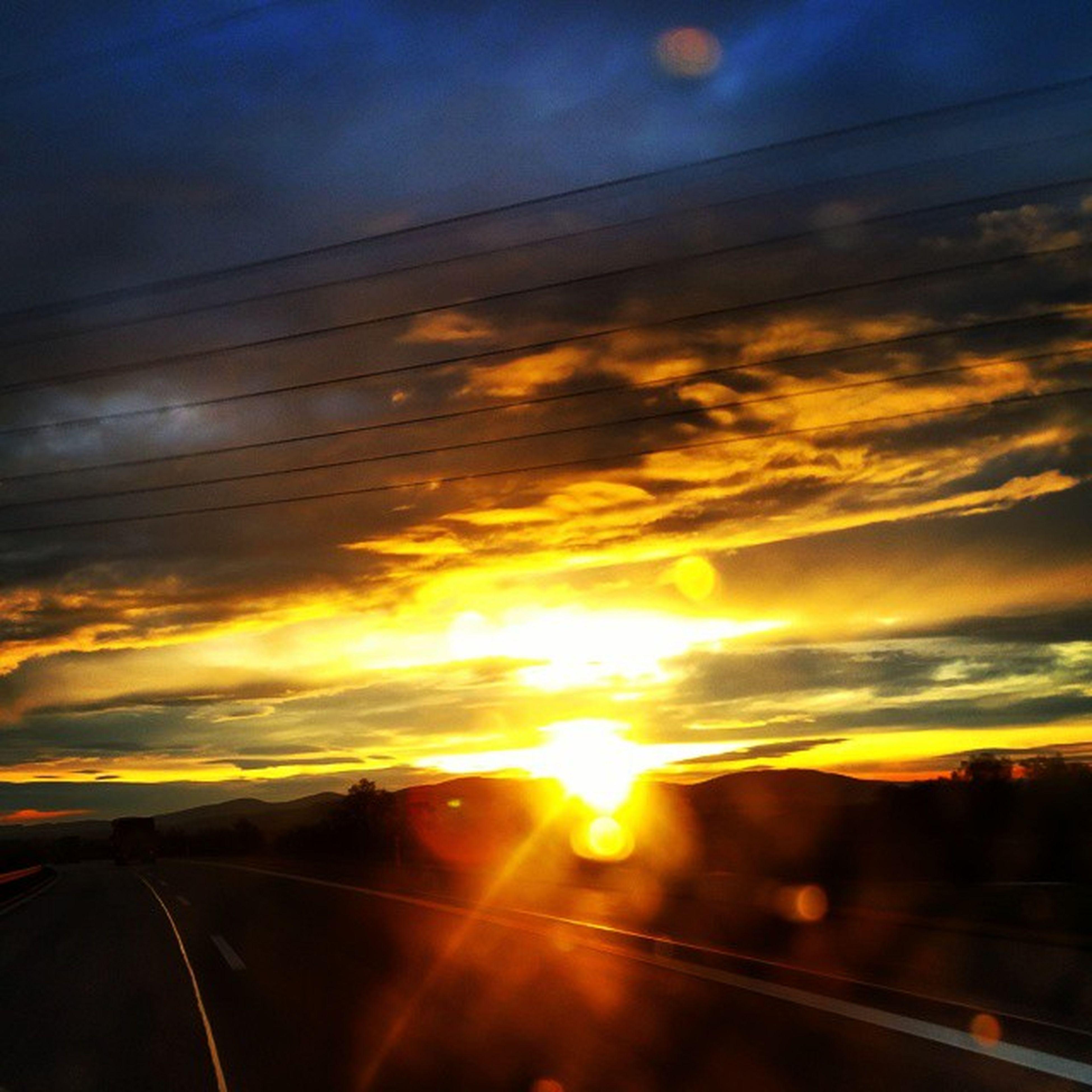 sunset, transportation, sky, cloud - sky, sun, road, scenics, beauty in nature, sunlight, orange color, nature, cloud, tranquility, tranquil scene, mode of transport, car, landscape, sunbeam, no people, outdoors