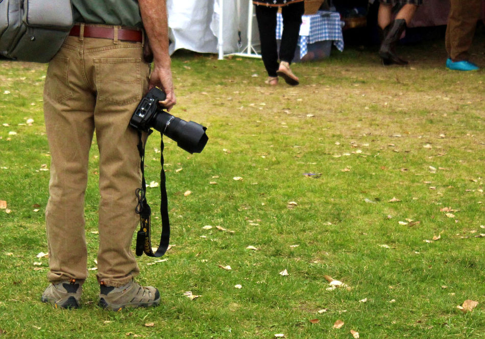 Photographer holding camera at side in park. At Side Camera Copy Space Equipment Freelance Freelance Life Grass In Between Lifestyles Low Section Men Park Person Photographer Photography Room For Text