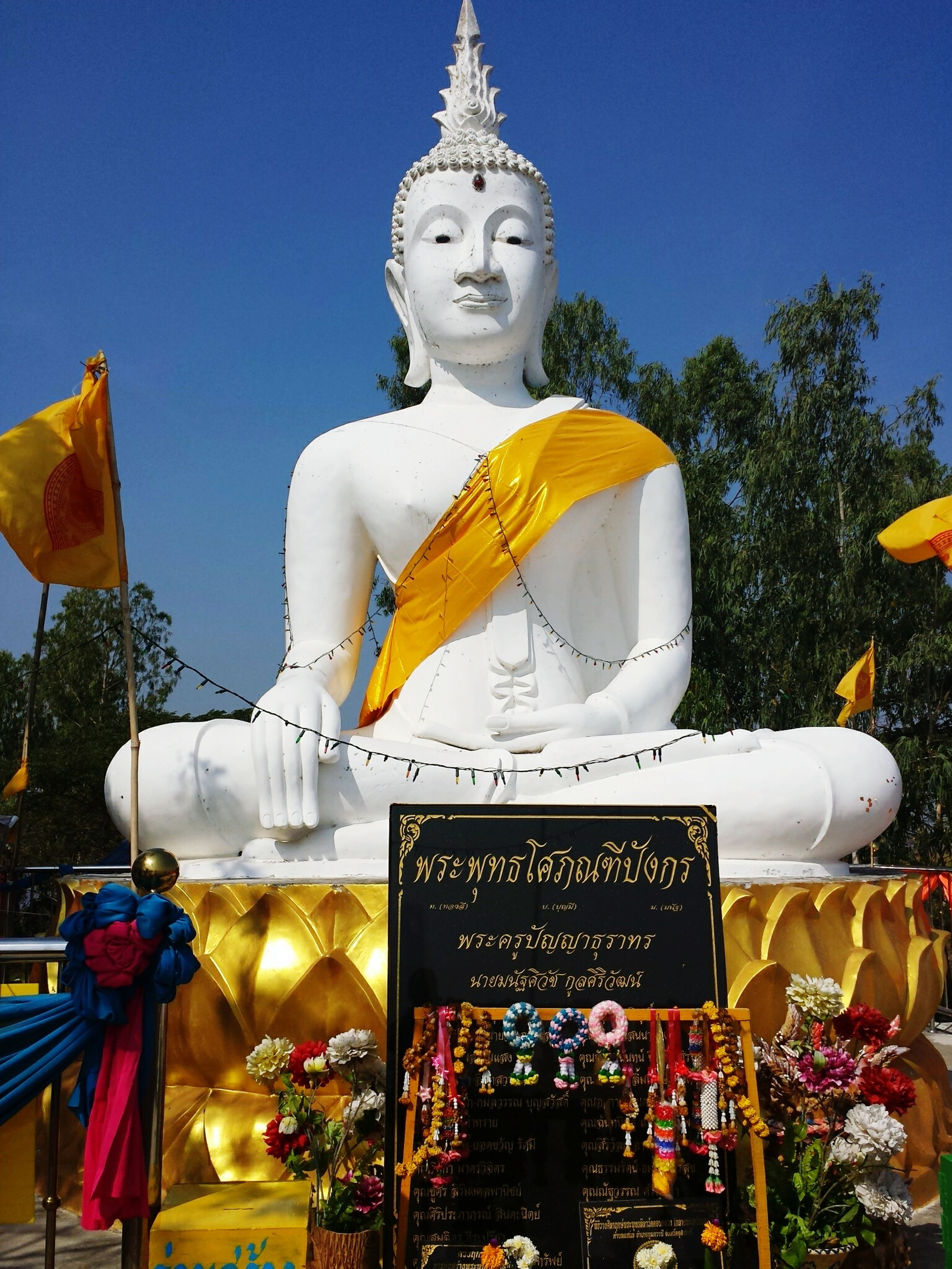 human representation, statue, sculpture, art and craft, art, creativity, religion, spirituality, buddha, animal representation, clear sky, text, carving - craft product, place of worship, yellow, craft, famous place