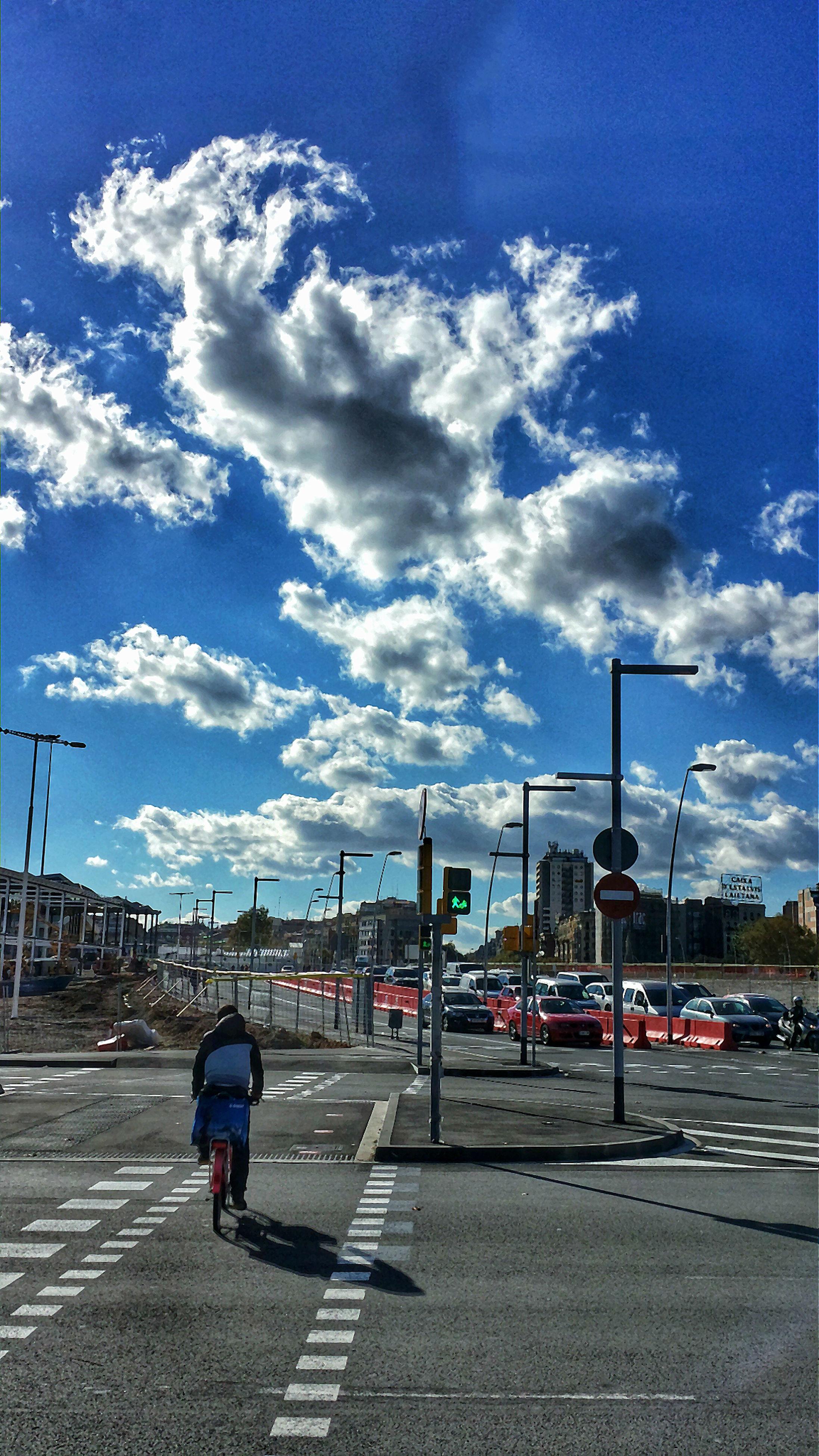 sky, transportation, street, street light, road, cloud - sky, built structure, mode of transport, blue, cloud, men, road marking, building exterior, architecture, city, car, the way forward, full length, walking