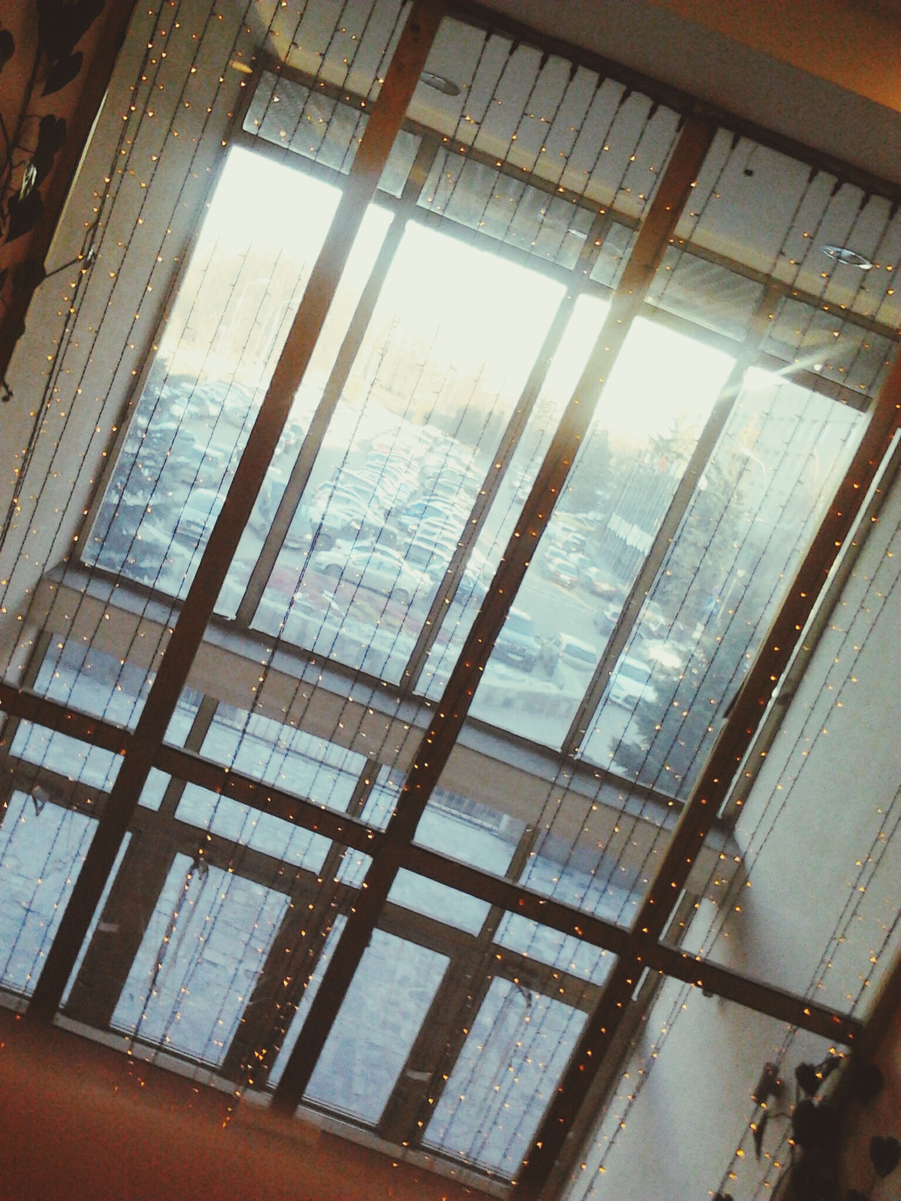 indoors, window, glass - material, transparent, architecture, built structure, ceiling, glass, sky, sunlight, low angle view, day, reflection, no people, modern, building, skylight, looking through window, water, interior