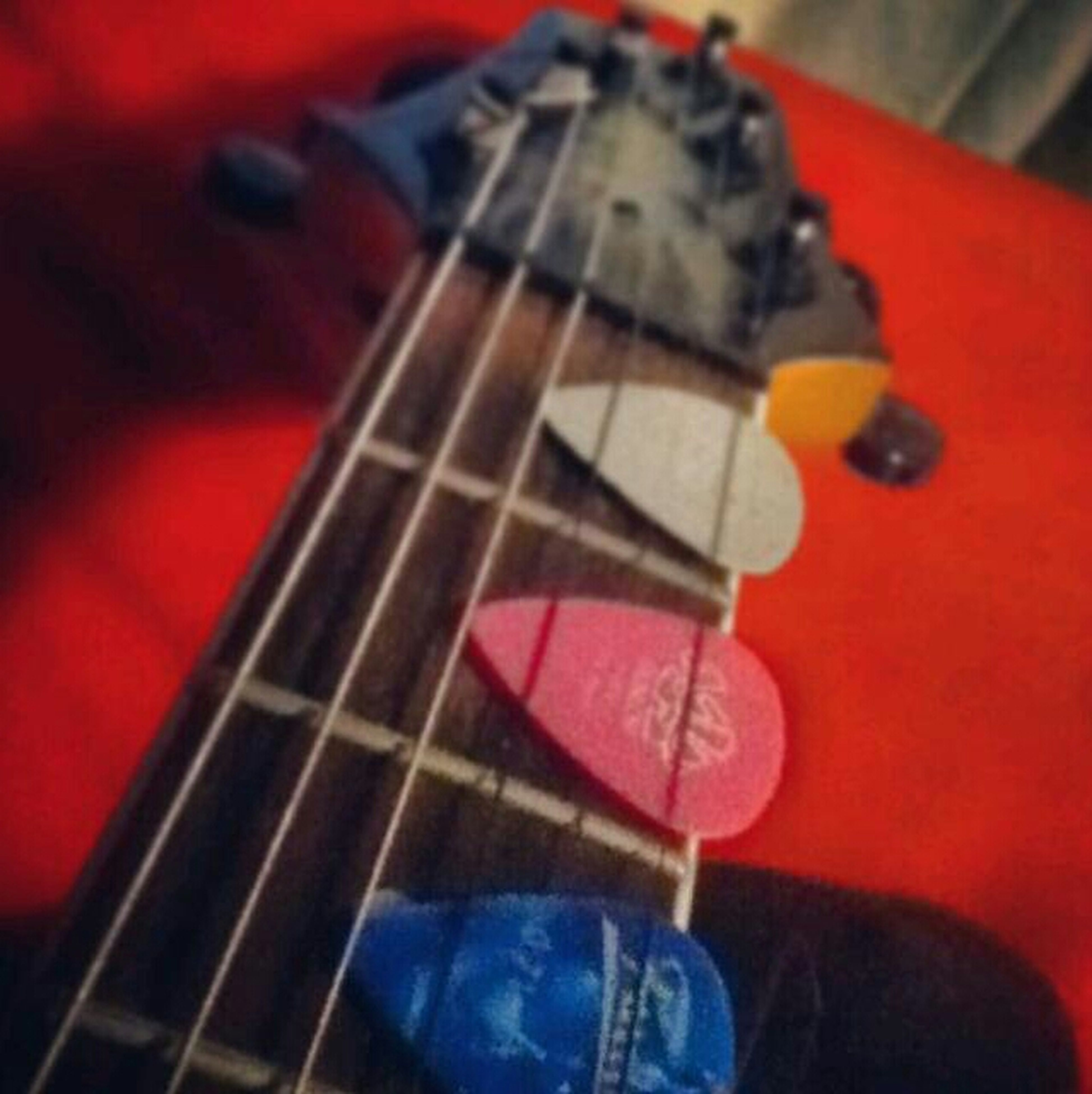 music, musical instrument, arts culture and entertainment, guitar, indoors, musical equipment, musical instrument string, selective focus, red, close-up, hobbies, focus on foreground, acoustic guitar, string instrument, part of, skill, playing, single object
