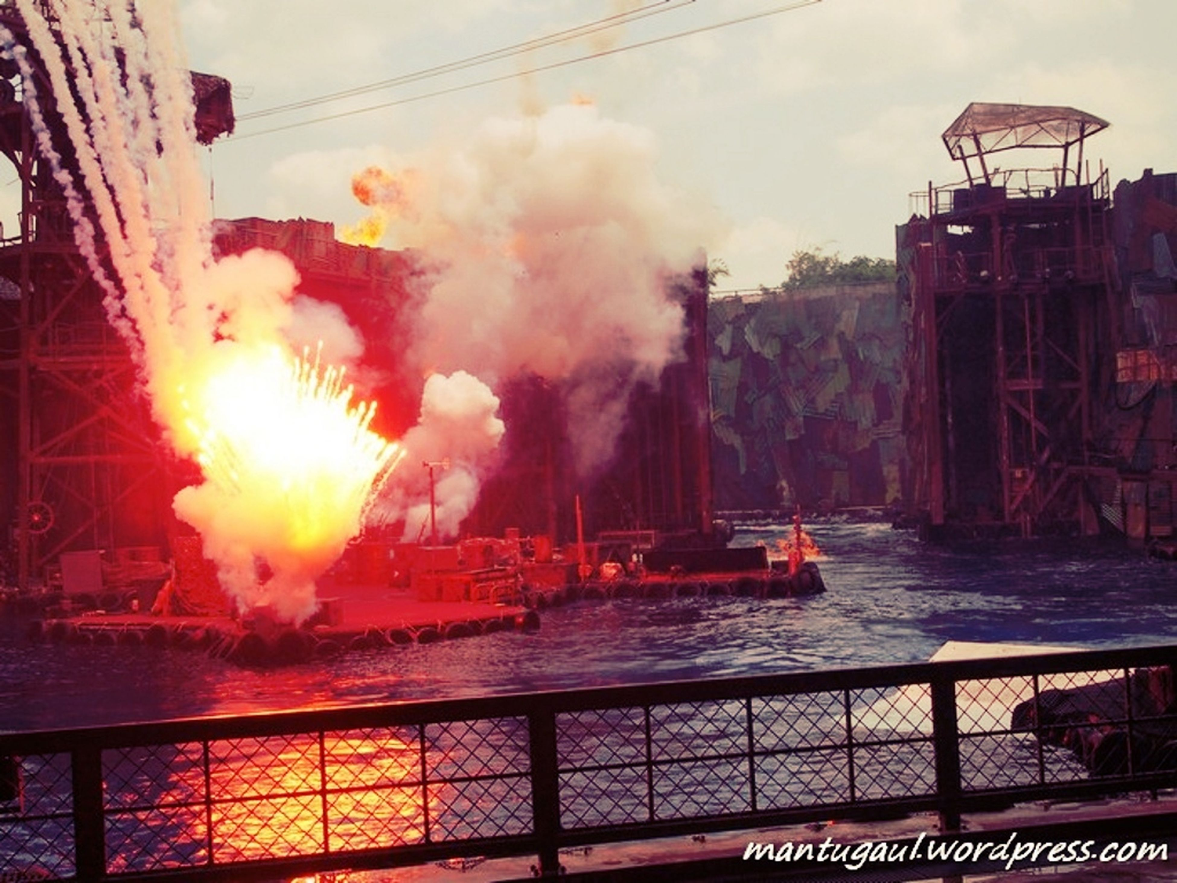 building exterior, built structure, sky, water, architecture, cloud - sky, smoke - physical structure, nautical vessel, crane - construction machinery, industry, transportation, outdoors, commercial dock, fire - natural phenomenon, sunset, harbor, flame, railing, burning, mode of transport