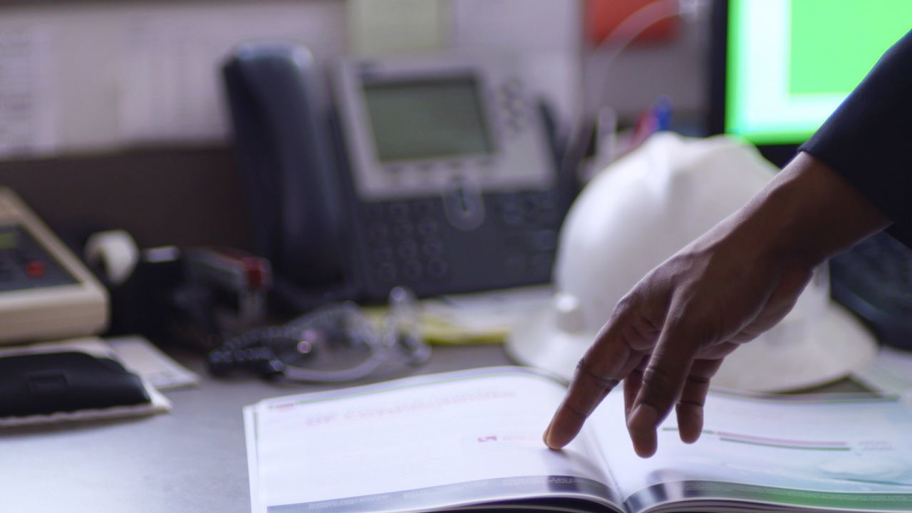 Office Desk hard hat Paperwork Real People One Person Indoors  Lifestyles Leisure Activity Women Home Interior Computer Technology Table Close-up Human Hand Human Body Part Day