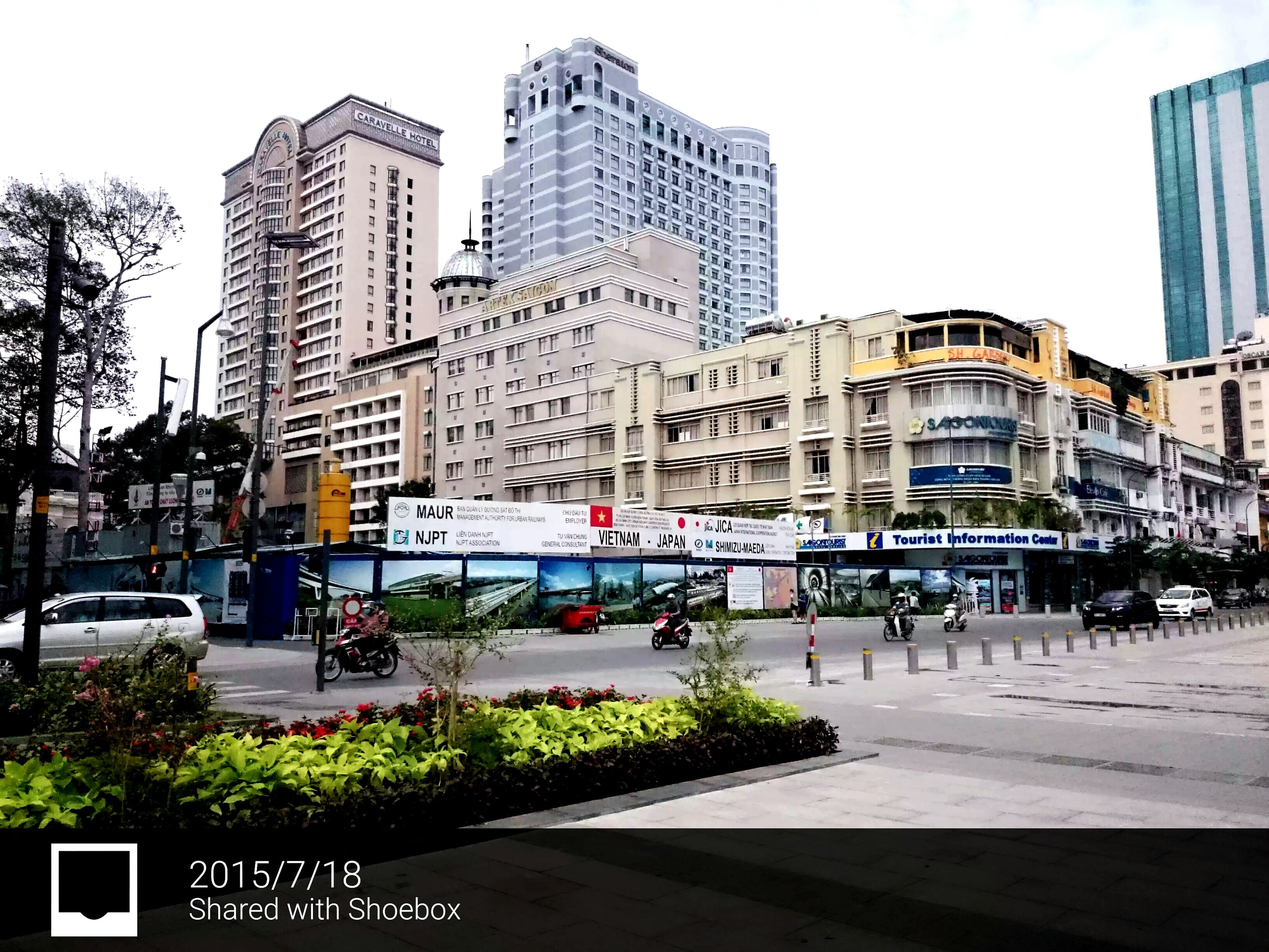 building exterior, architecture, transportation, city, built structure, car, mode of transport, land vehicle, street, city life, city street, traffic, road, incidental people, building, text, public transportation, clear sky, bus, sky