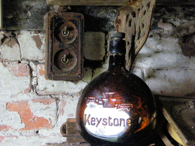 Antique Brown Glass Close-up Day Deterioration Glass Bottle Keystone Light Switch Machine Part Machinery Metal Metallic No People Nostalgia Obsolete Old Old Building  Old-fashioned Run-down Rusty The Past Vintage White Washed Wall Wine Bottle