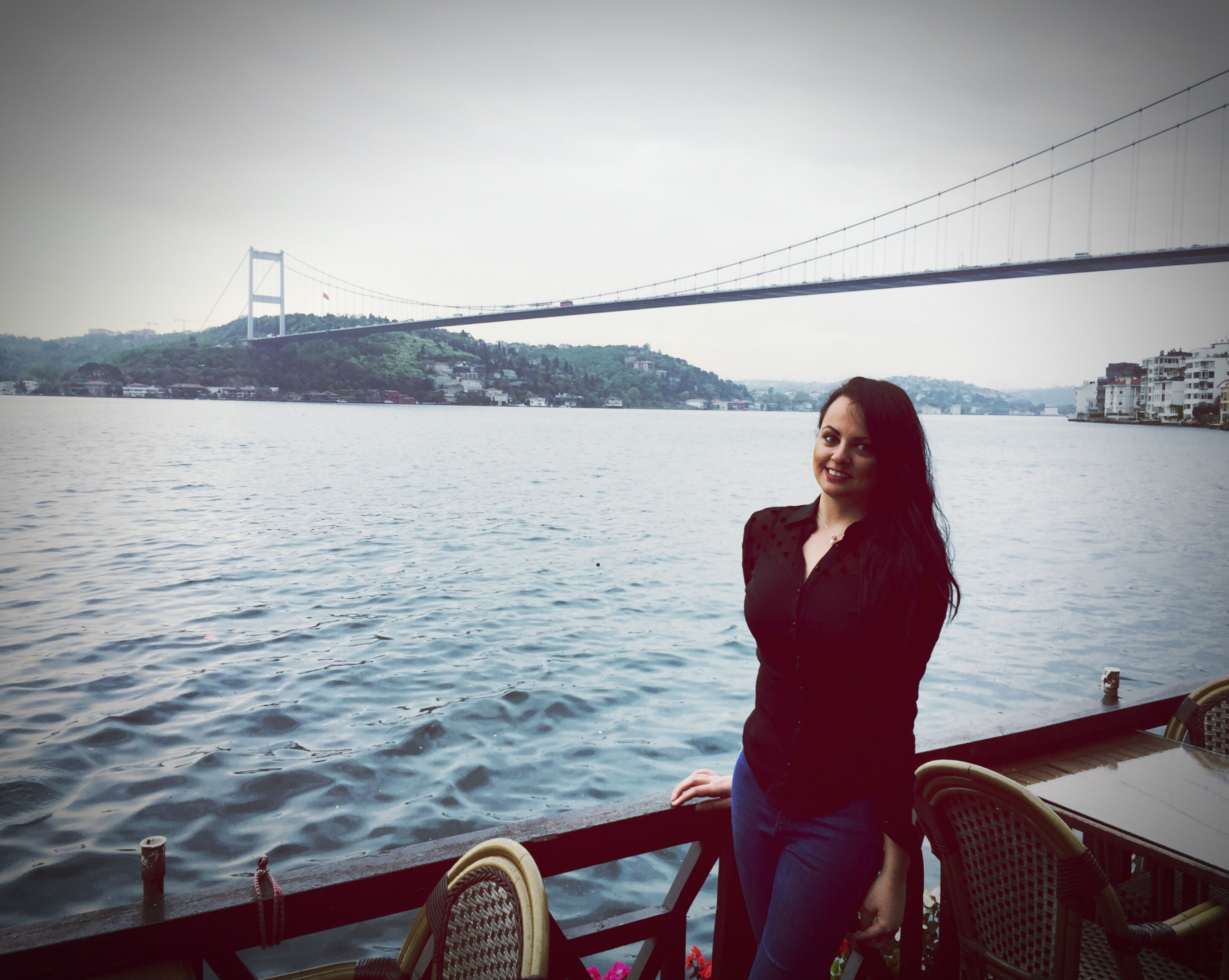 bridge - man made structure, connection, river, suspension bridge, water, real people, railing, transportation, one person, bridge, young adult, architecture, lifestyles, leisure activity, built structure, sky, outdoors, young women, nautical vessel, day, smiling, beautiful woman, city, nature