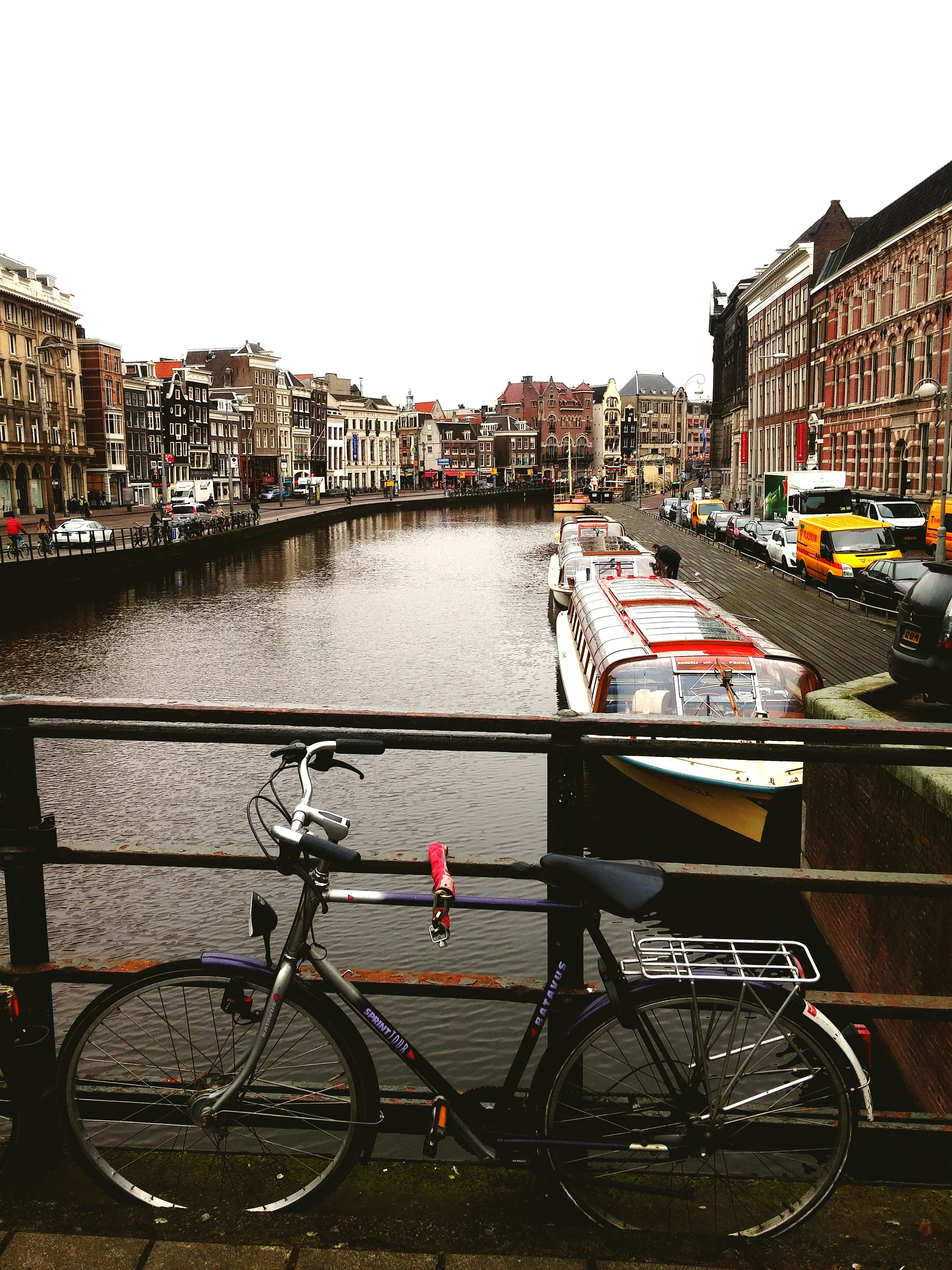 building exterior, transportation, architecture, mode of transport, built structure, bicycle, land vehicle, water, city, canal, parked, nautical vessel, stationary, parking, clear sky, river, railing, street, boat, travel