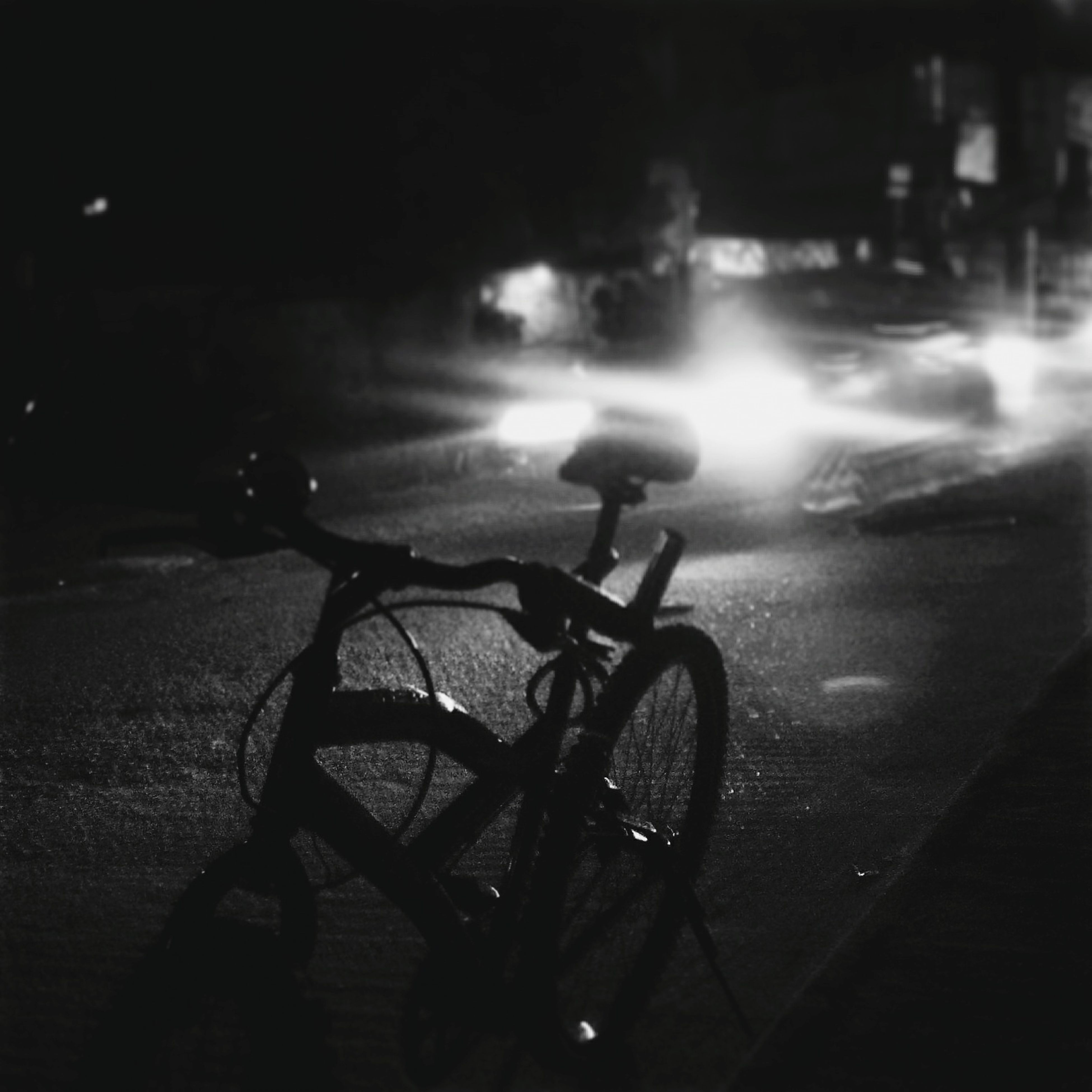 bicycle, night, land vehicle, transportation, mode of transport, illuminated, street, parking, stationary, parked, shadow, dark, sunlight, silhouette, road, car, outdoors, no people, sidewalk, absence
