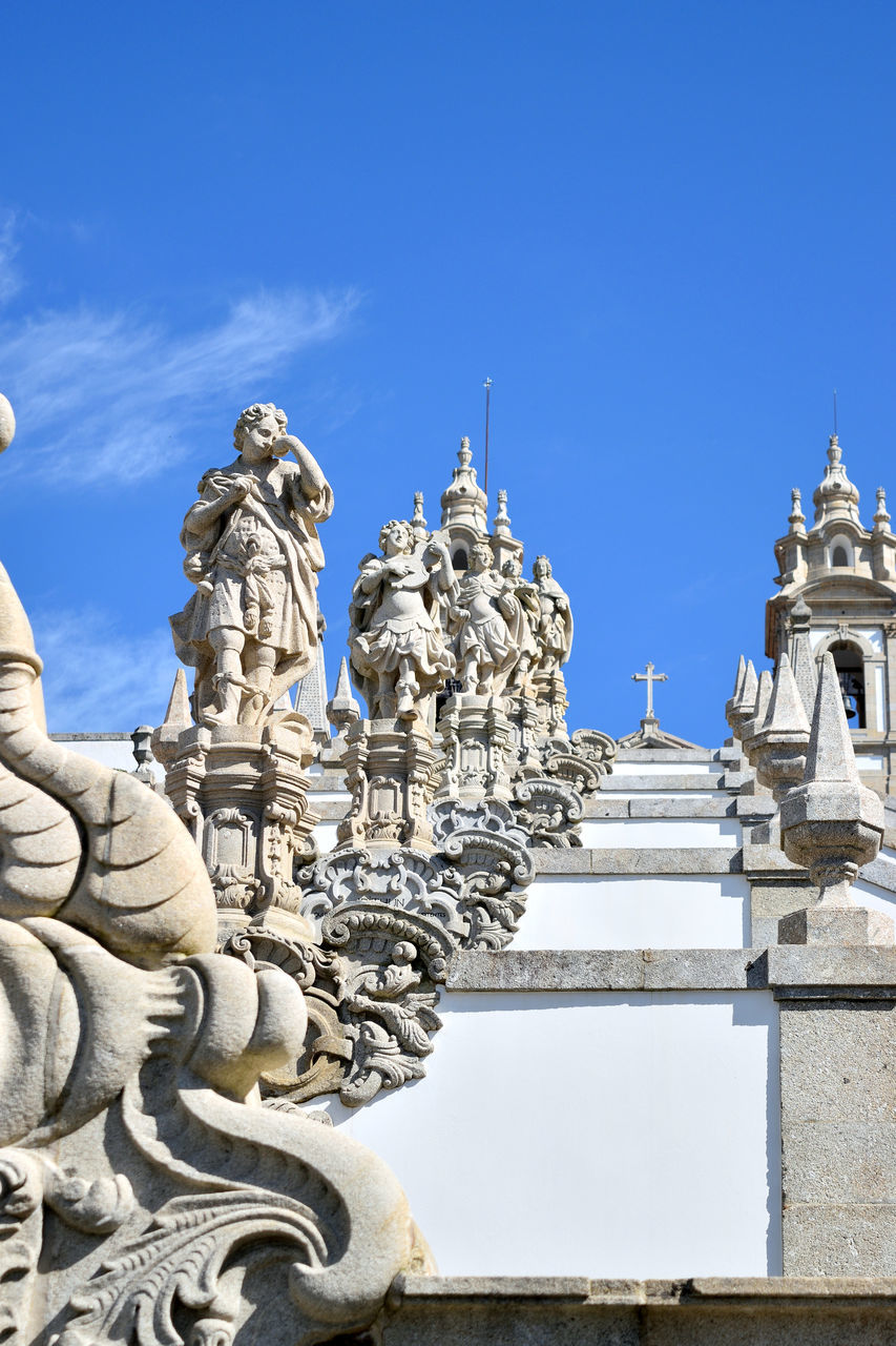 sculpture, statue, art and craft, outdoors, religion, low angle view, building exterior, day, sky, spirituality, architecture, built structure, travel destinations, place of worship, no people, cloud - sky