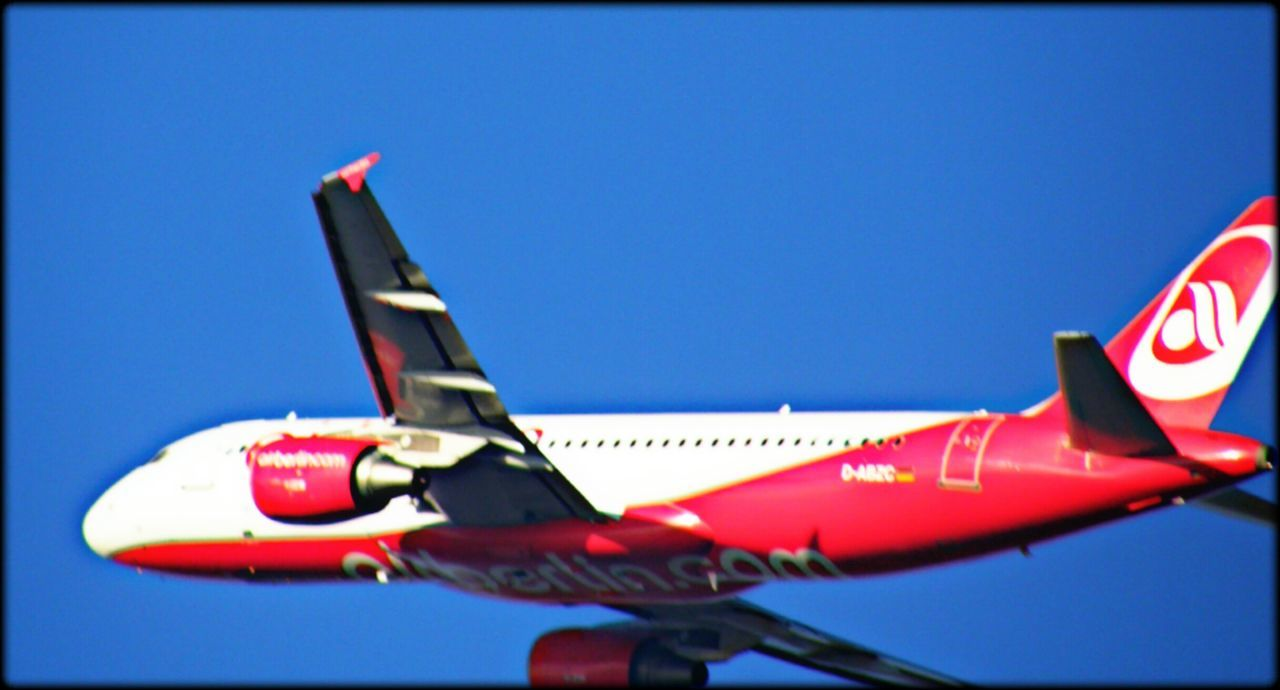 red, clear sky, no people, blue, transportation, day, airplane, air vehicle, outdoors, close-up, sky