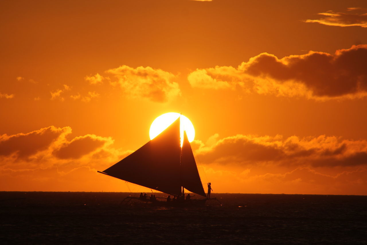 Silhouette Of Sailboat In Sea At Sunset