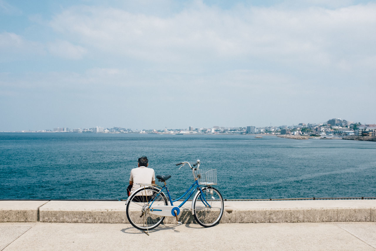 Rear View Of Man With Bicycle On Promenade By Sea Against Cloudy Sky