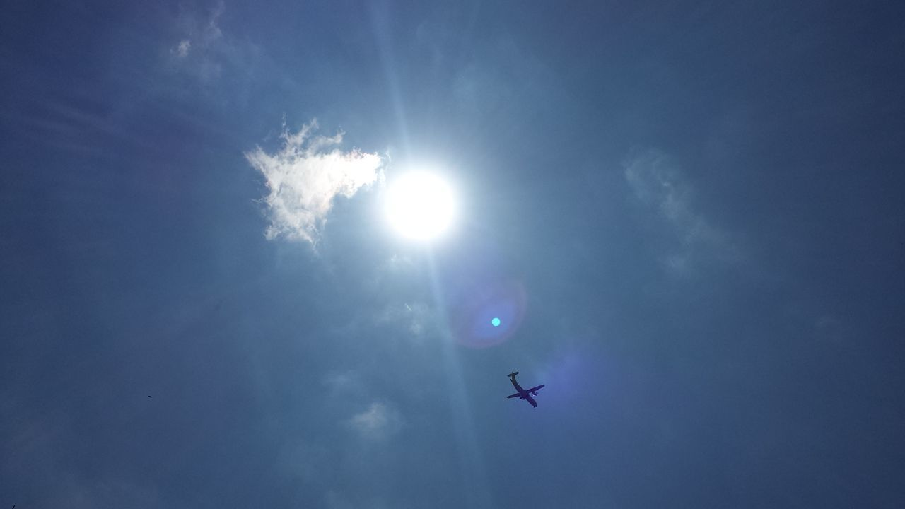 low angle view, sky, sun, sunbeam, flying, blue, sunlight, mid-air, outdoors, no people, day, nature, airplane, beauty in nature, airshow, vapor trail