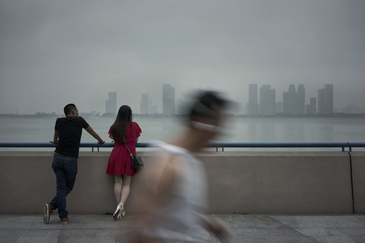 Couple and a runner along the Hangzhou river in the early morning Adults Only Blurred Motion Building Exterior City Cityscape Females Full Length Motion Outdoors People Rear View Sea Skyscraper Togetherness Two People Urban Skyline Walking Water