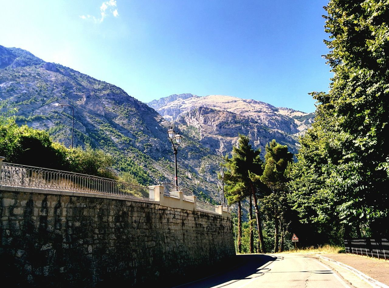 Road By Wall Against Mountains