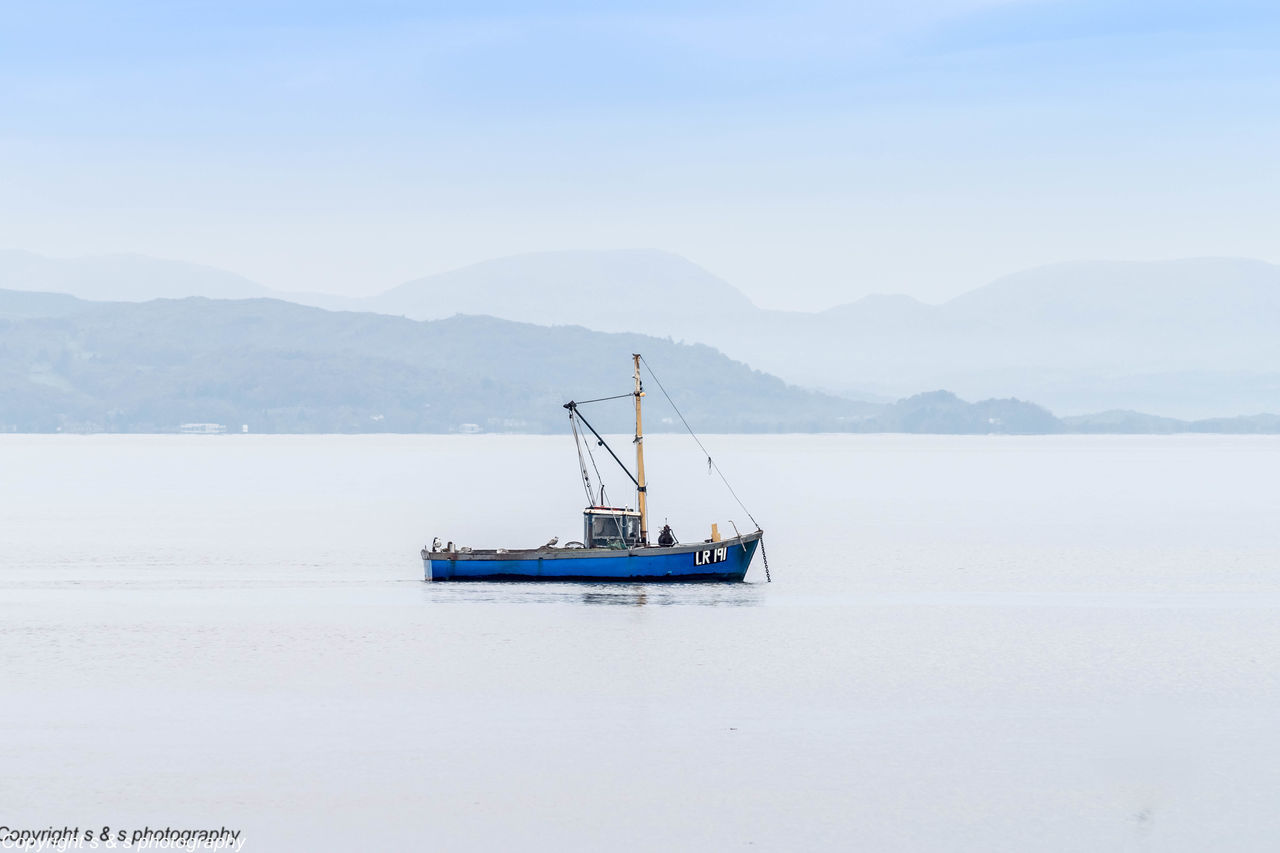 a beautiful scene in morecambe bay Blue Boat Boats British Seaside Fishing Boat Morecambebay Mountains And Sky Reflection Water_collection