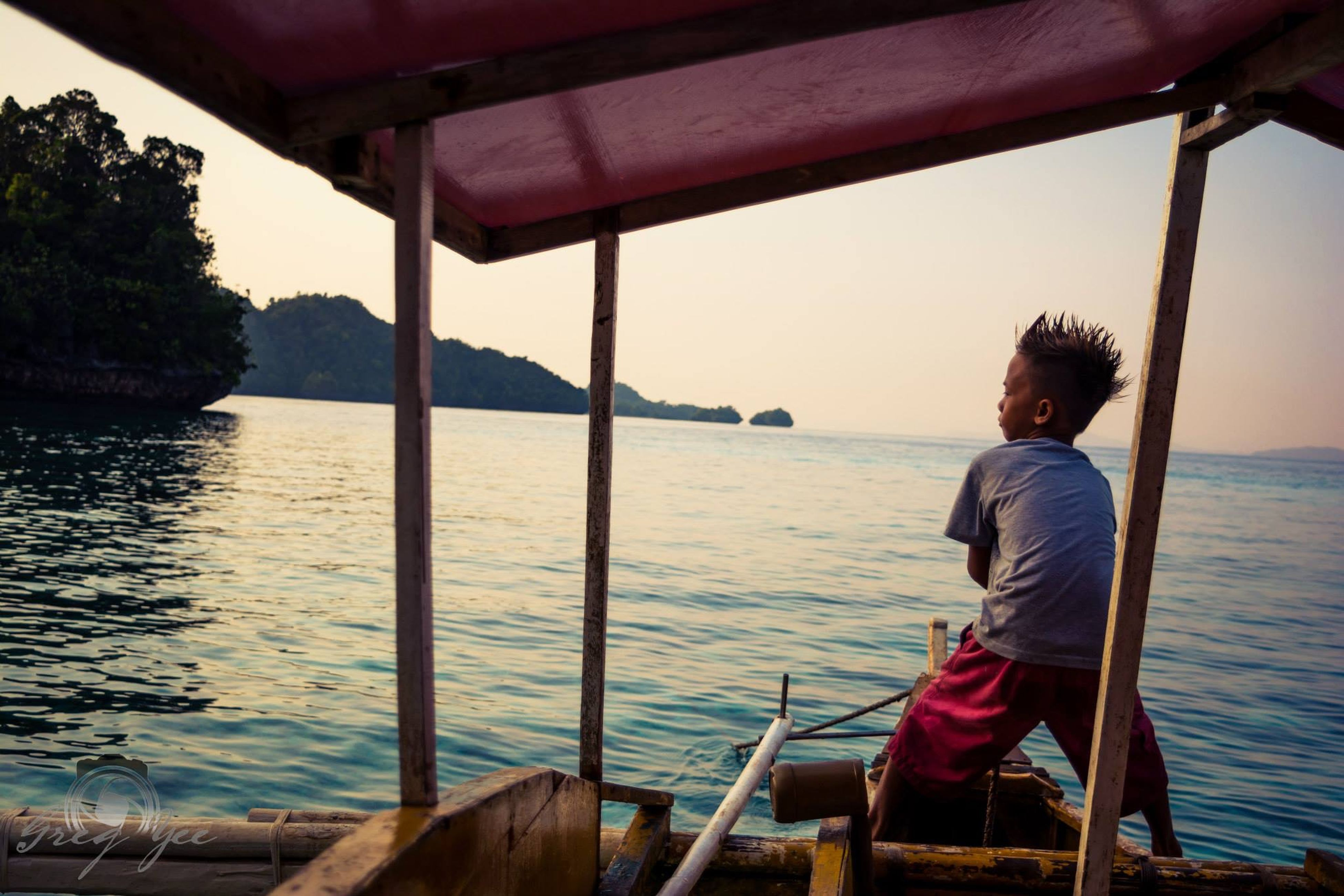 water, rear view, sea, lifestyles, leisure activity, casual clothing, nature, sitting, scenics, tree, beauty in nature, standing, tranquility, sky, nautical vessel, tranquil scene, three quarter length, vacations