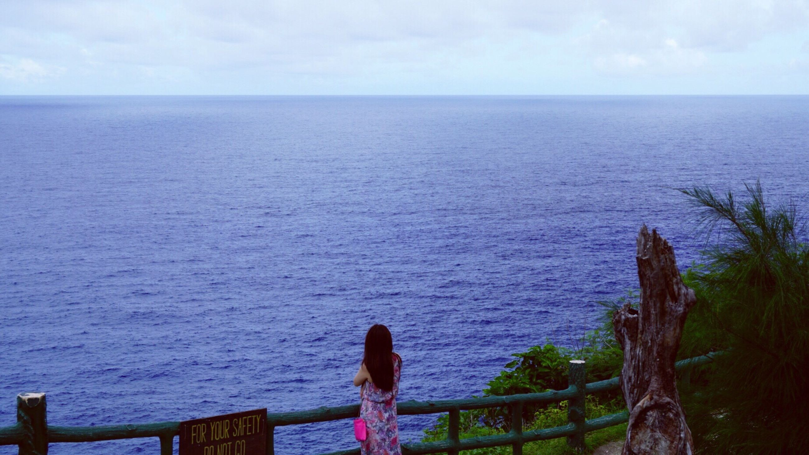 water, sea, horizon over water, tranquil scene, scenics, tranquility, beach, beauty in nature, railing, sky, standing, men, rear view, tourist, seascape, tourism, nature, shore, cloud - sky, hobbies, remote, in front of, blue, vacations, distant, outdoors, day, getting away from it all