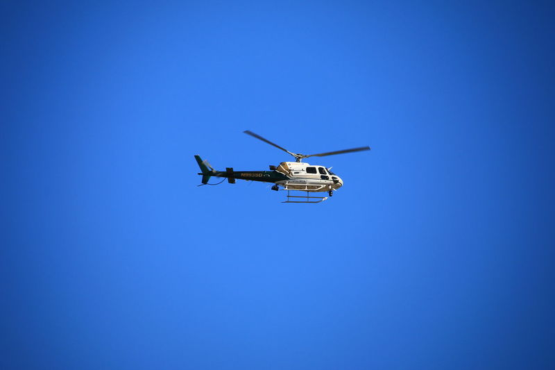 The sheriffs helicopter searching for something against a blue sky. Aerospace Industry Air Vehicle Blue Clear Sky Flying Helicopter Low Angle View No People Outdoors Police Police At Work Police Helicopter Sheriff Sky Transportation