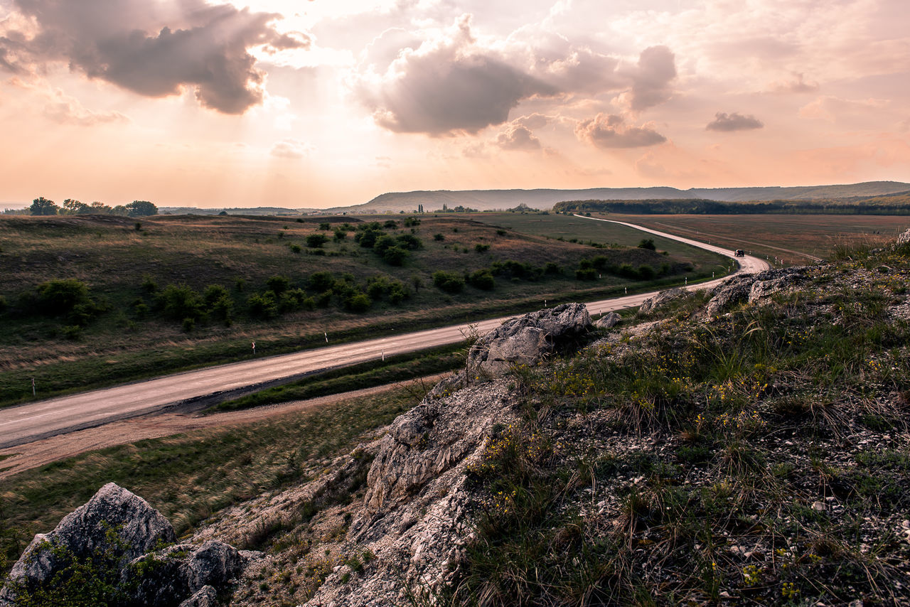 On rigid roads Cloud - Sky Sunset Dramatic Sky Landscape Beauty In Nature Outdoors Field Scenics Sky Grass Nature No People Day Car Truck Road Bend Bending Roads Hill Hilltop Rock Rocks