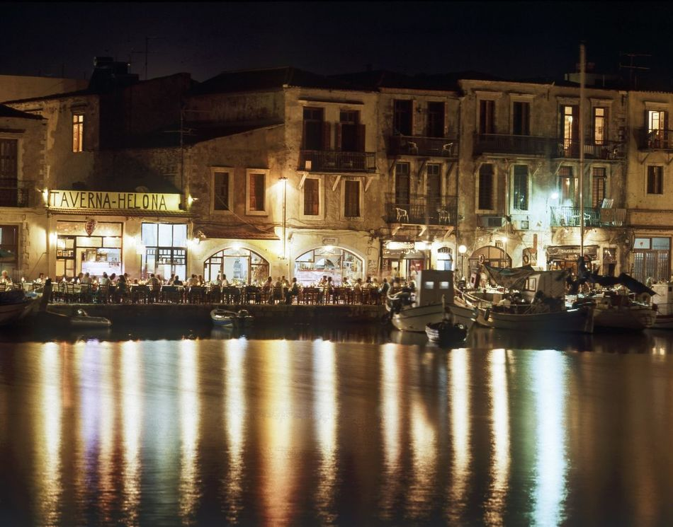 Harbourside restaurants at night, Rethymnon Old Town, Crete, Greece Alfresco Eating Architecture Culture And Tradition Dining Evening Greece, Crete Greek Restaurant Greek Taverna Harbourside Holidays Illuminated Illuminated Buildings Night Outdoors Reflection Rethymnon Rethymnon Crete Tourism Destination Tourists Traditional Culture Travel Destinations Travel Photography Vacation Venetian Water
