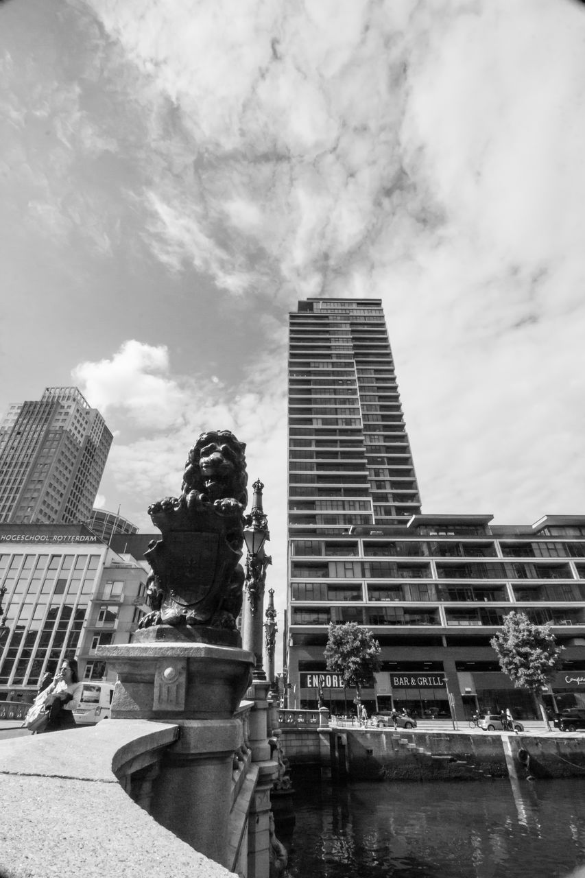 building exterior, architecture, sky, built structure, cloud - sky, statue, sculpture, day, outdoors, low angle view, water, skyscraper, no people, modern, city
