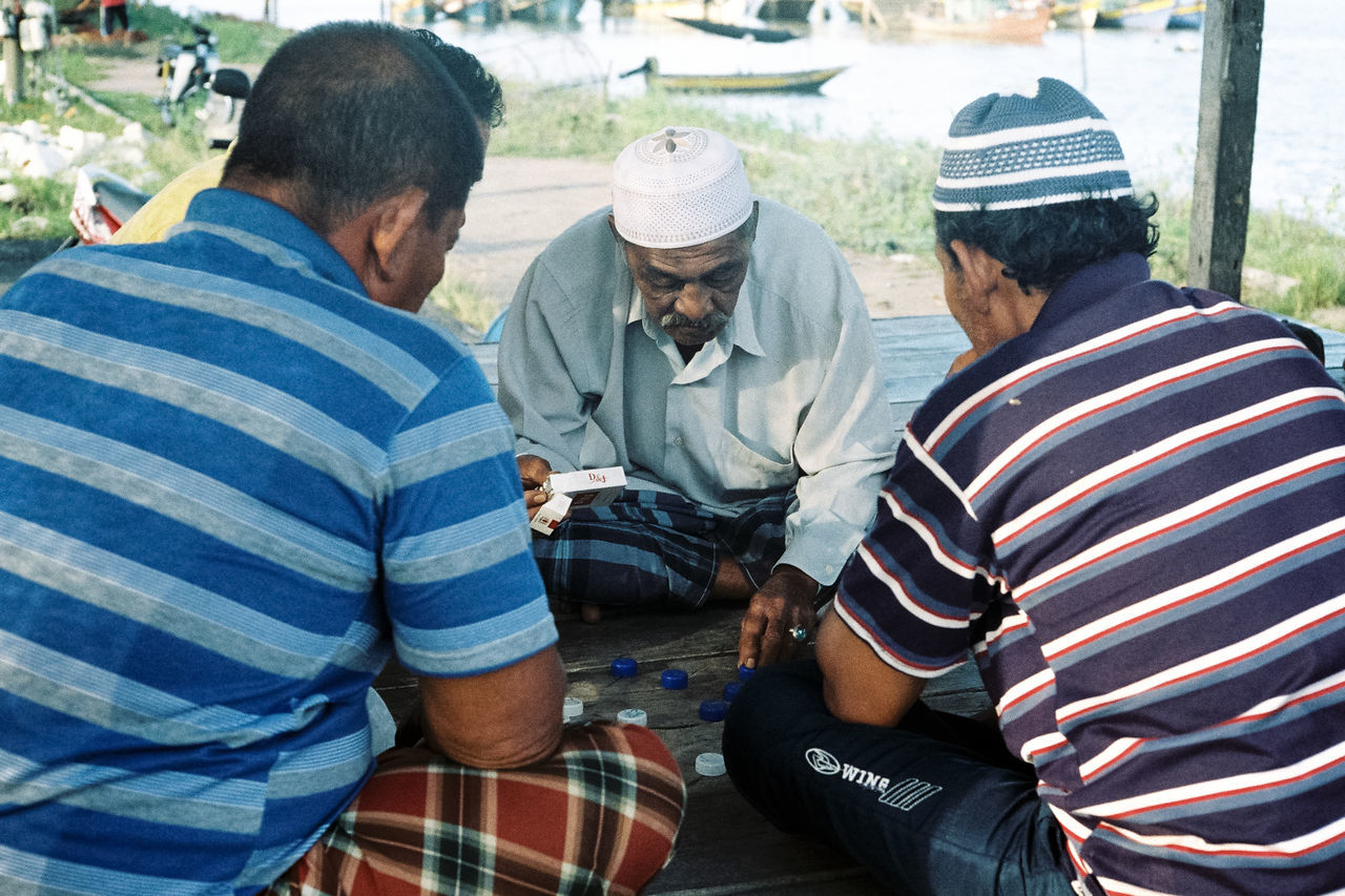Bonding Casual Clothing Checkers Community Day Family Fishing Village Friendship Leisure Activity Lifestyles Medium Group Of People Men Off Season Outdoors Relaxation Sitting Togetherness People And Places