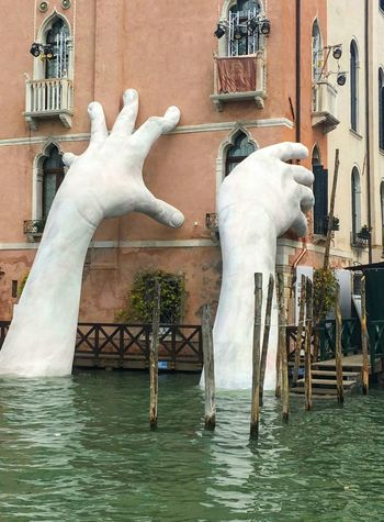 These big hands climbing up the building in Venice are to highlight climate change ... Water Statue Sculpture Building Exterior
