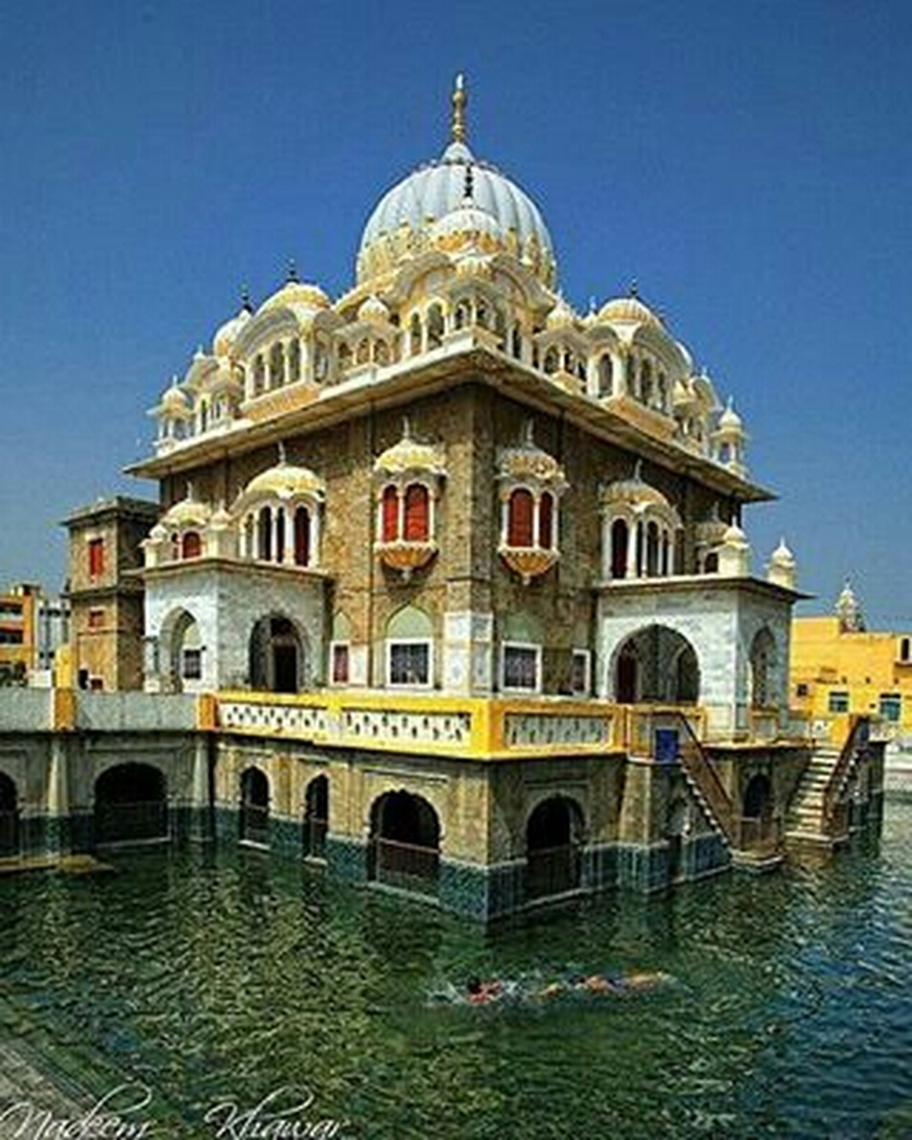 architecture, built structure, building exterior, water, famous place, dome, travel destinations, religion, clear sky, place of worship, tourism, waterfront, travel, spirituality, arch, church, blue, facade, history